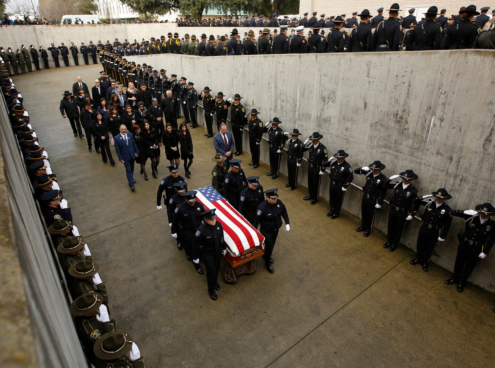Family members follow the flag-draped coffin of Davis Police Officer Natalie Corona before her funeral at the University of California, Davis, Friday, Jan. 18, 2019, in Davis, Calif. Corona was was shot and killed Jan. 10 responding to scene of a three-car crash in Davis.  Police say gunman Kevin Douglas Limbaugh, 48, not involved in the crash,  rode up on a bicycle and without warning, opened fire on Corona.
