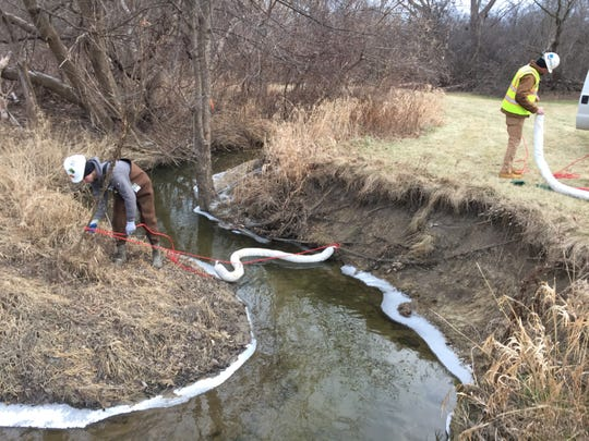 Workers place absorbent blooms in the Plumbrook Drain in Sterling Heights to soak up an oily liquid found in the water.