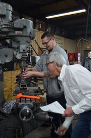Mark Dyer, an Epic CNC Training Academy instructor and journeyman tool and die maker, ensures that a part produced by Epic Machine machinist Clifford Oseland, left, will meet customer specifications. Oseland completed Epic's CNC academy training course for milling in December and now works full time for the company.