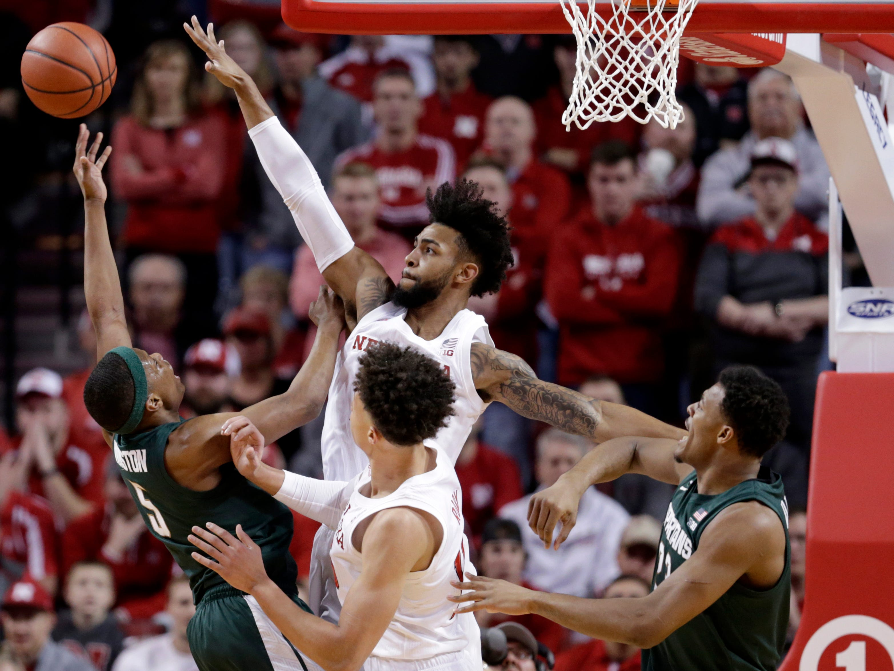 Nebraska's Isaac Copeland Jr., center rear, tries to block a shot by Michigan State's Cassius Winston (5), as Xavier Tillman, right, and Isaiah Roby, center front, watch, during the first half.