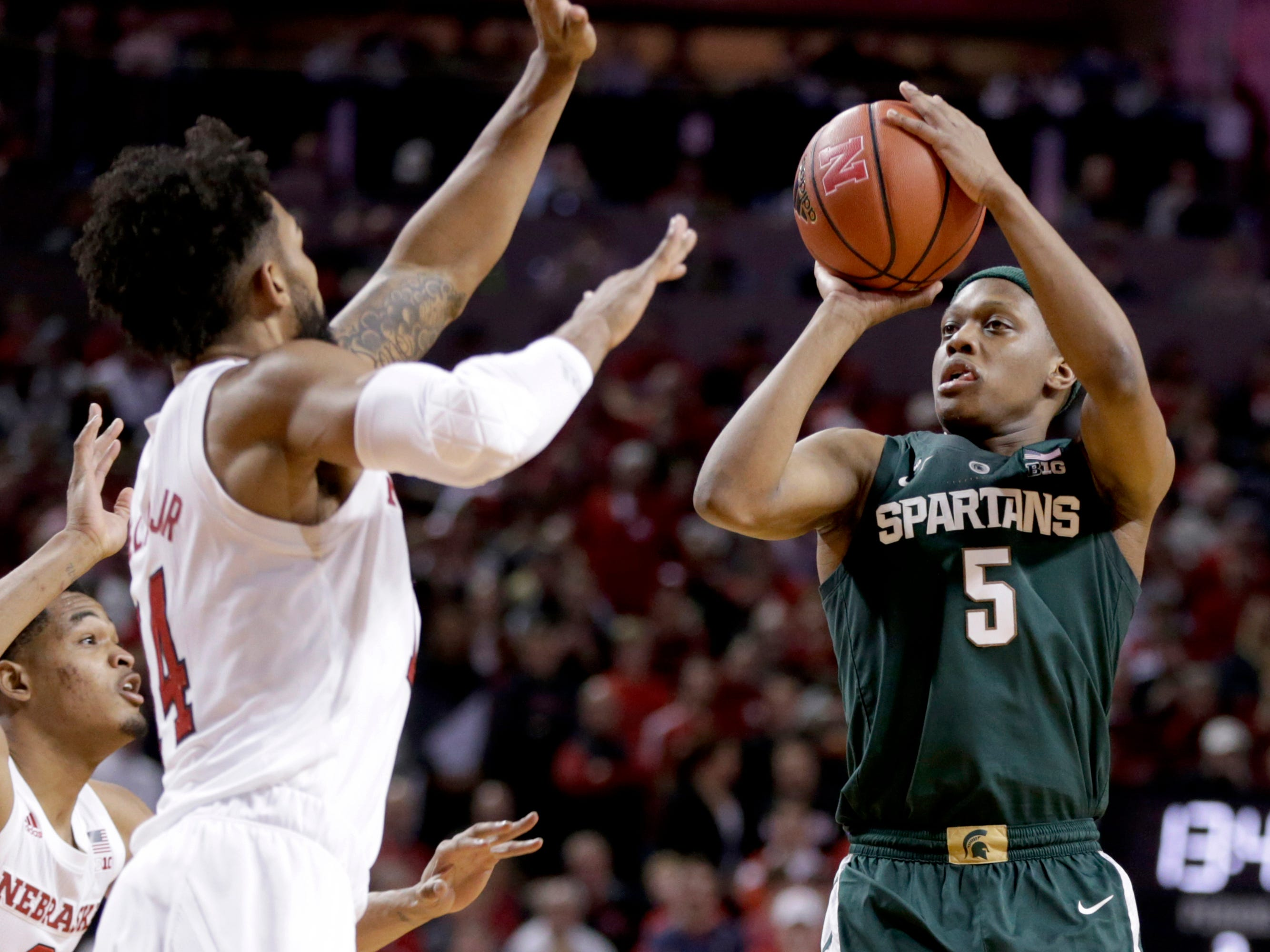 Michigan State's Cassius Winston (5) shoots against Nebraska's James Palmer Jr (0) and Isaac Copeland Jr. (14) during the second half.