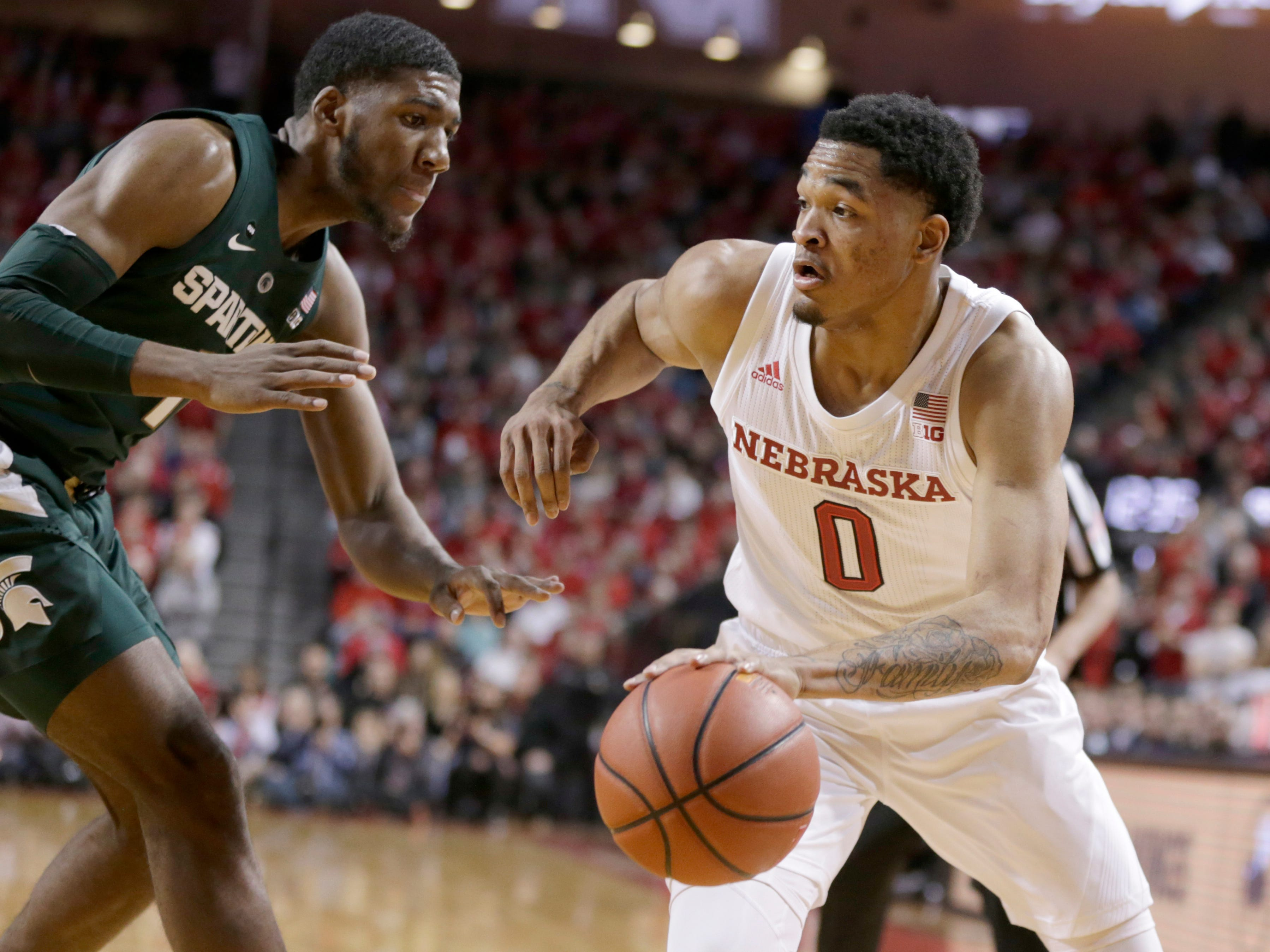 Nebraska's James Palmer Jr (0) drives round Michigan State's Aaron Henry (11) during the first half.