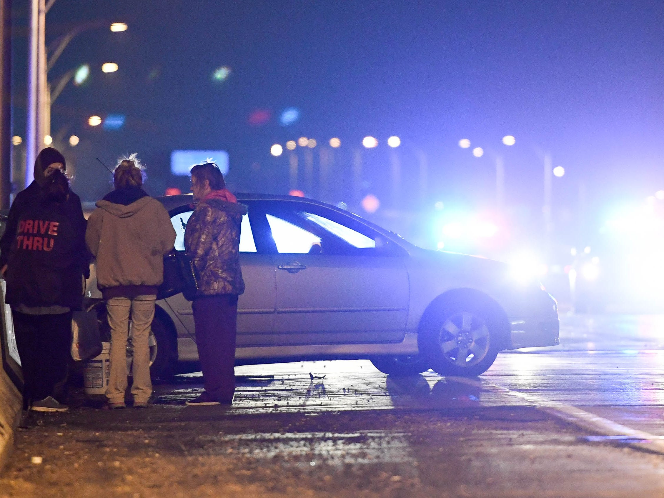People involved in a rush-hour crash on the Westbound Lloyd Expressway at the Mary Street overpass wait by their vehicle as emergency workers work to clear the closed expressway Thursday, January 17, 2019.