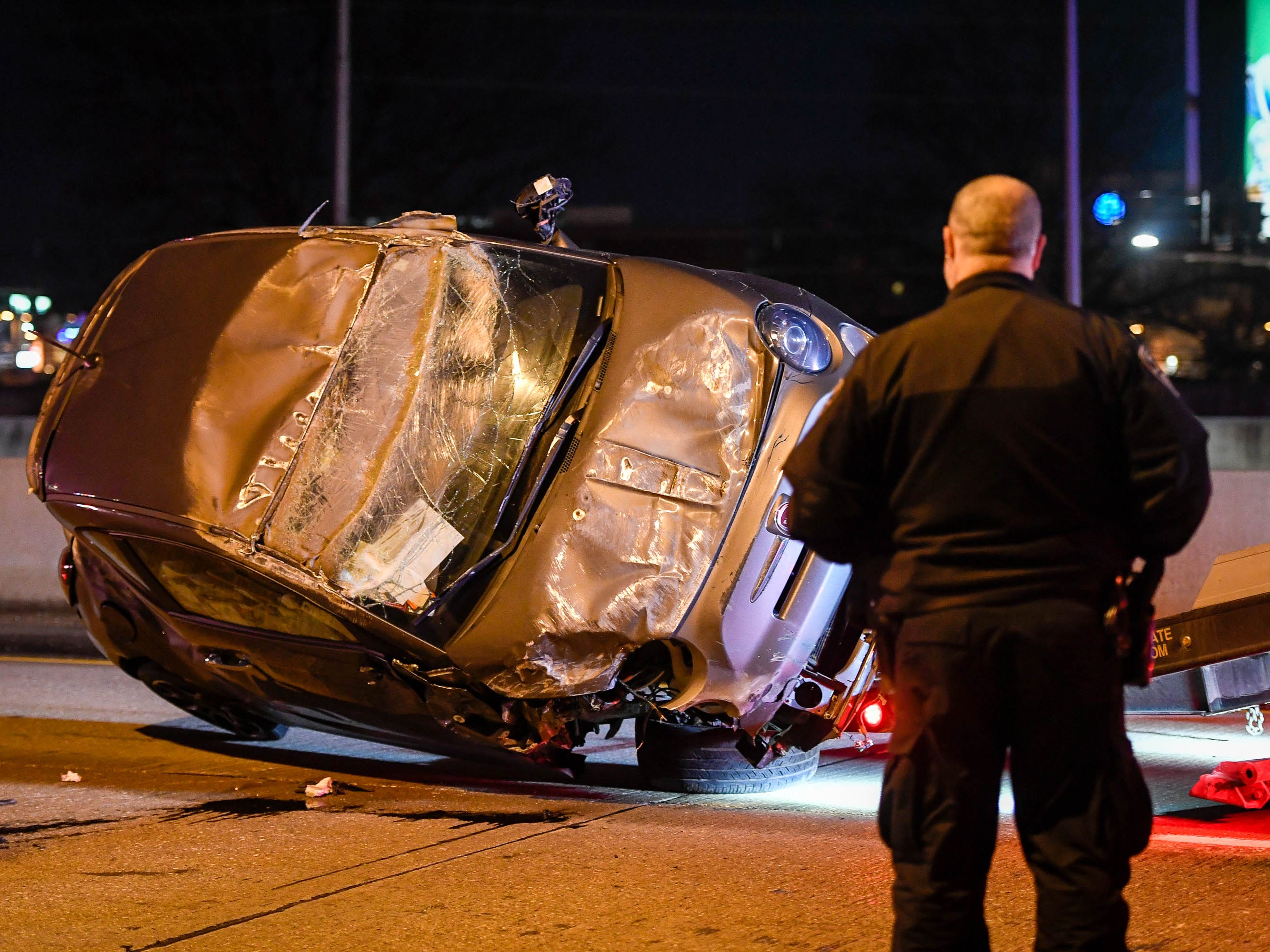Evansville Police officer watches as one of the vehicles, involved in a rush-hour crash that closed the Westbound Lloyd Expressway at the Mary Street overpass, is loaded on to a flatbed truck Thursday, January 17, 2019.