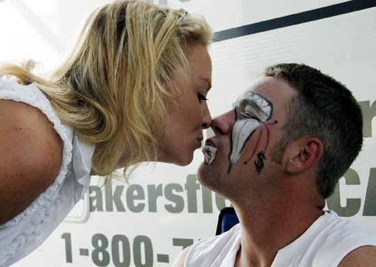 Severance rodeo bullfighter Lance Brittan receives a kiss from wife, Cami, before the Greeley Stampede in 2003.