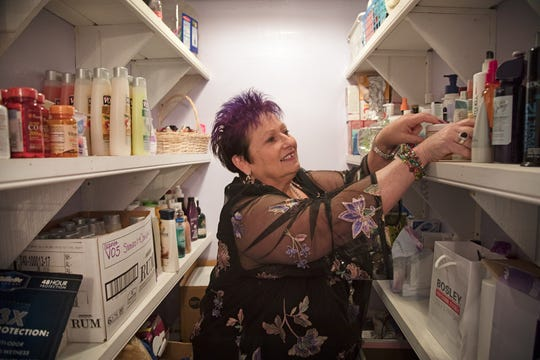 Jeannie Turner reaches for hygiene products stocked for women in need in a back room of her Fort Myers thrift store, Second Chance. The store is a major source of funding for her ministry, One Way Out, which she founded 20 years ago to help women in trouble.
