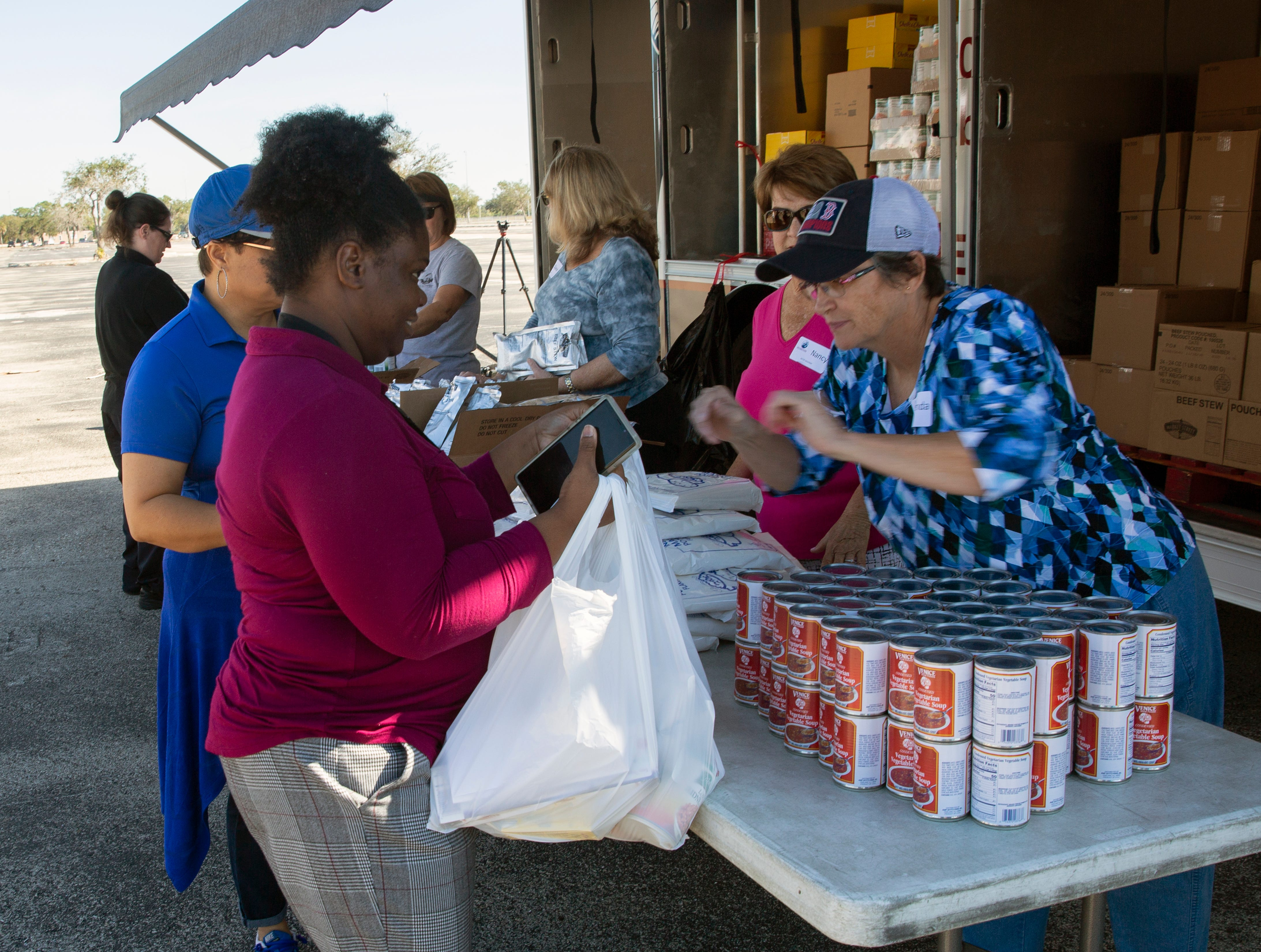 Volunteers distribute food to furloughed federal employees and airport workers, Friday, Jan. 18, 2019, at the Southwest Florida International Airport in Fort Myers.