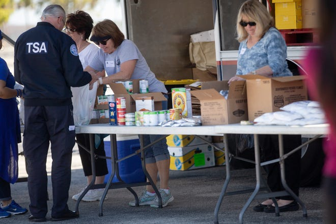 Harry Chapin Food Bank volunteers distribute food, Friday, Jan. 18, 2019, at the Southwest Florida International Airport in Fort Myers.