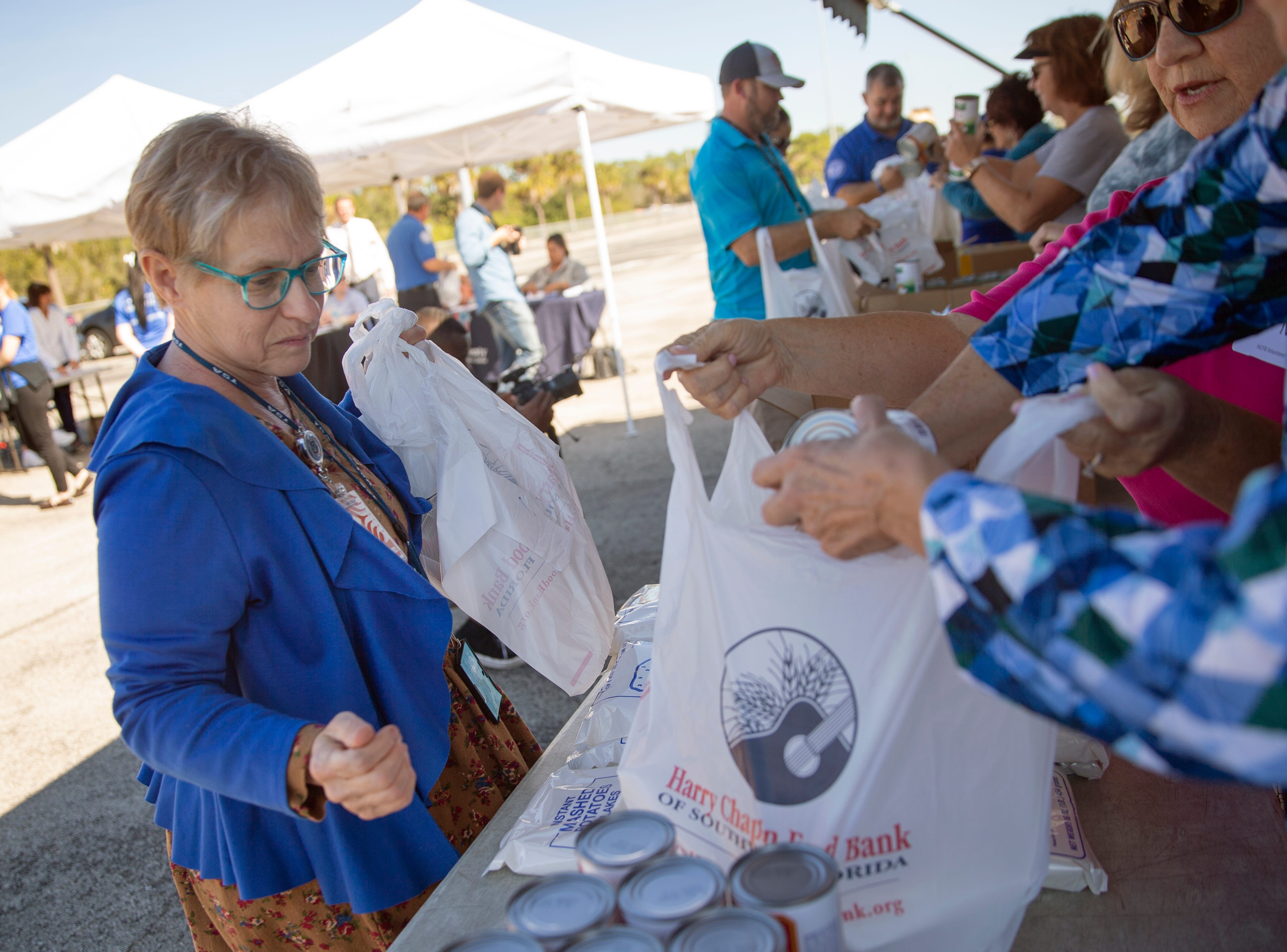 An airport employee receives food from volunteers with the Harry Chapin Food Bank, Friday, Jan. 18, 2019, at the Southwest Florida International Airport in Fort Myers.