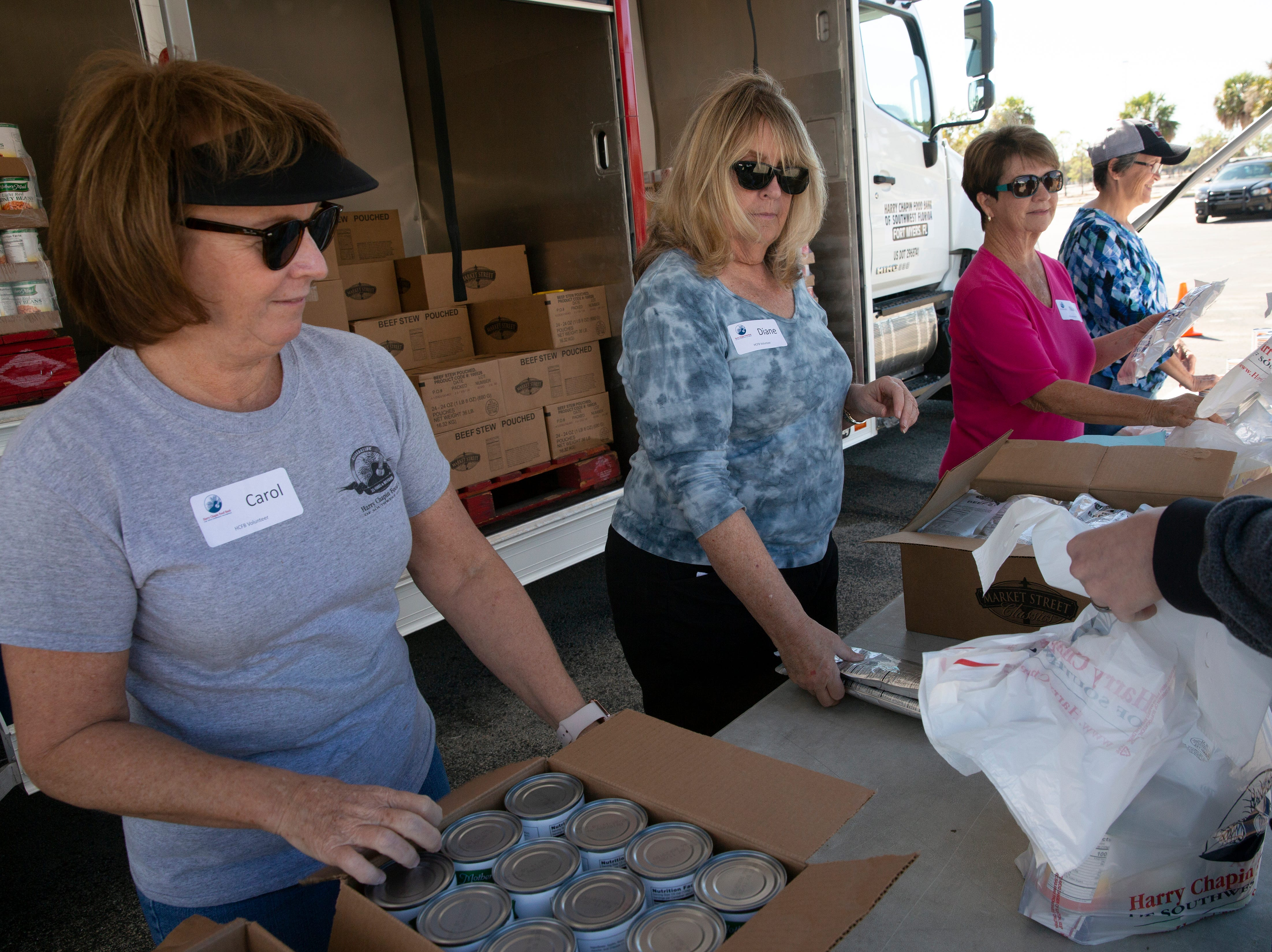 Volunteers Diane O, Connell, second from left,  Nancy Francis and Brenda Hurd distribute food, Friday, Jan. 18, 2019, at the Southwest Florida International Airport in Fort Myers.