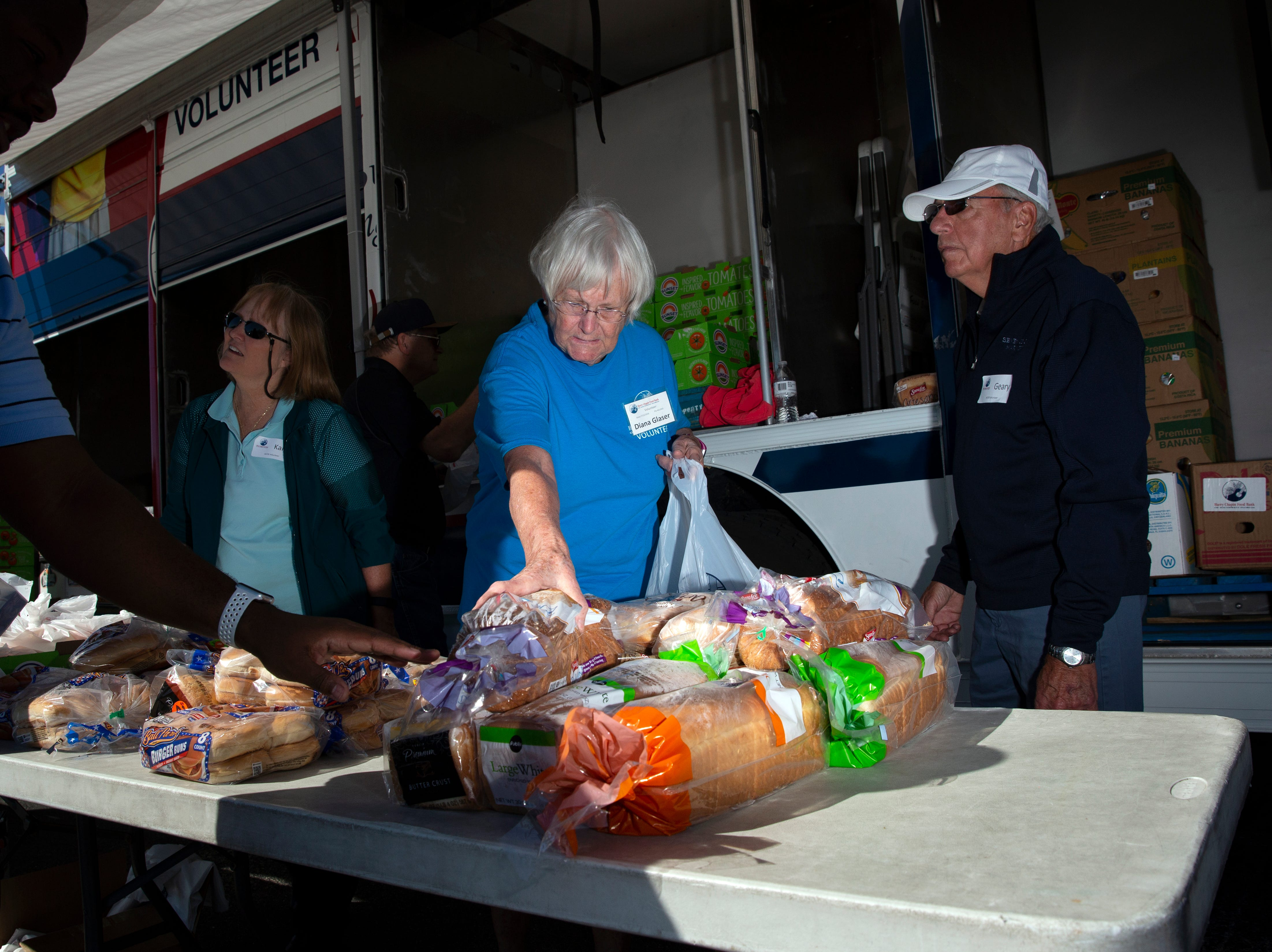 Harry Chapin Food Bank volunteers, Karen Medhurst, left, Diana Glaser, center, and Geary Francis distribute food, Friday, Jan. 18, 2019, at the Southwest Florida International Airport in Fort Myers.