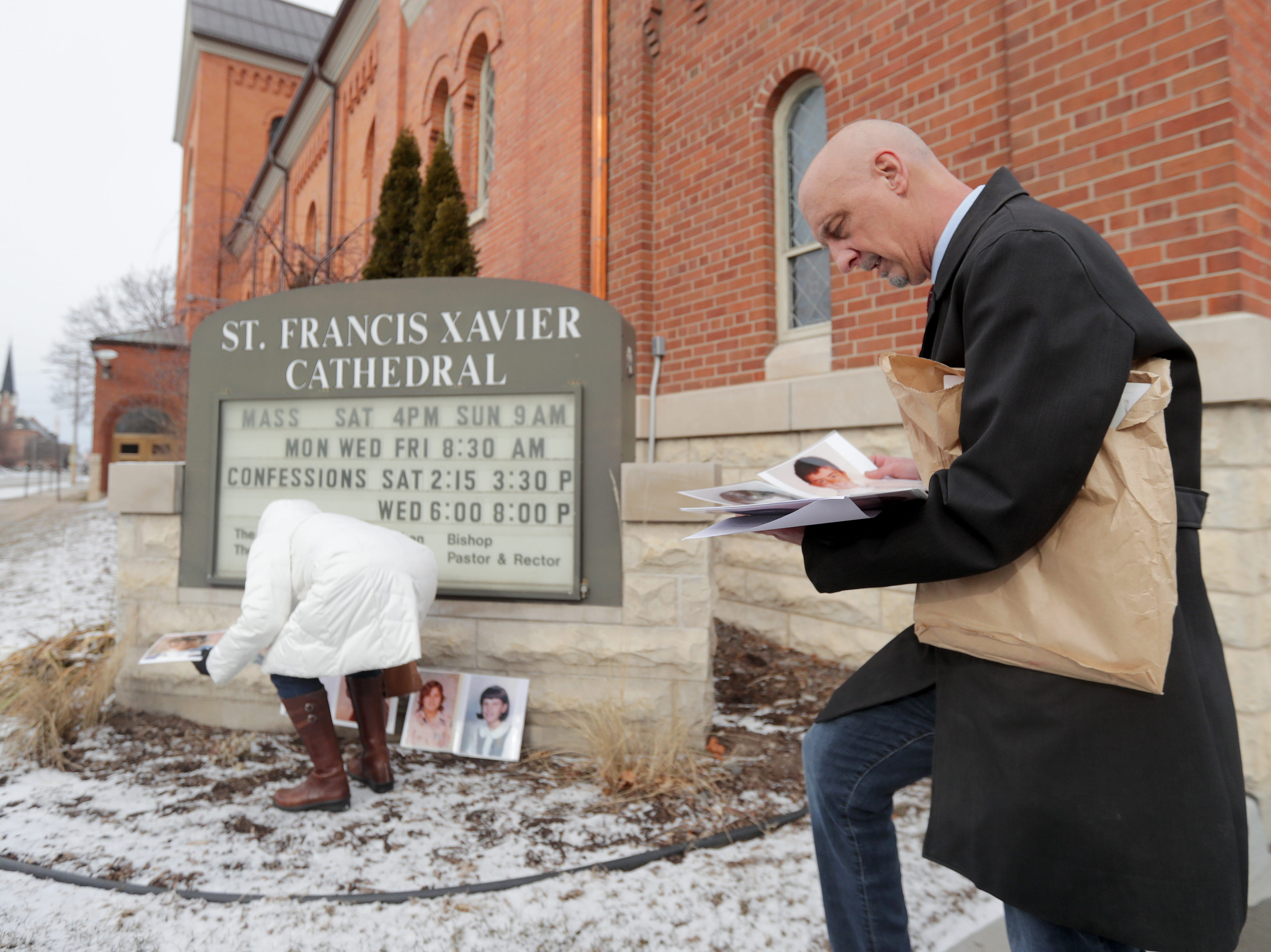 Peter Isely of Survivors Network for those Abused by Priests, looks at photos of abuse victims prior to a Jan. 18 press conference at of St. Francis Xavier Cathedral.