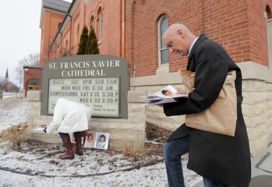 Peter Isely of Survivors Network for those Abused by Priests, looks at photos of abuse victim Friday in front of St. Francis Xavier Cathedral during a press conference in Green Bay.