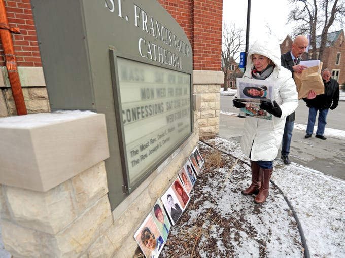 Alice Hodek, mother of a Green Bay sexual abuse victim, displays photos of children abused by priests in front of St. Francis Xavier Cathedral, before a press conference Thursday with Peter Isely of Survivors Network for those Abused by Priests, in background.