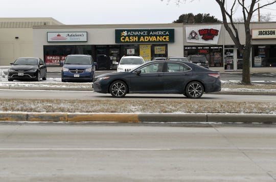 A car drives past businesses along Military Avenue on Friday in Green Bay. The business corridor will see the loss of Shopko and Sears within a year's time.