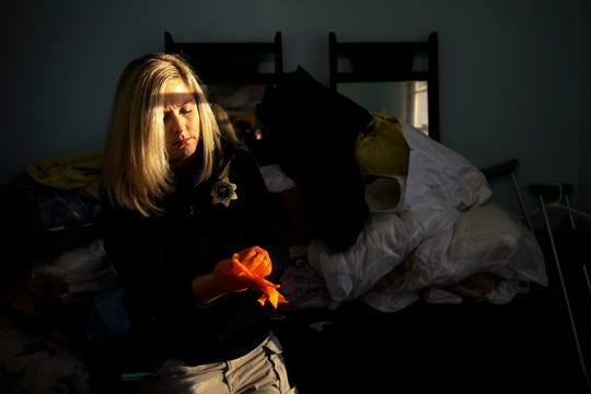 Jennifer Cason of the Greenville County Coroner's Office puts on a new set of gloves as she works the scene of a natural death on Tuesday, Jan. 15, 2019