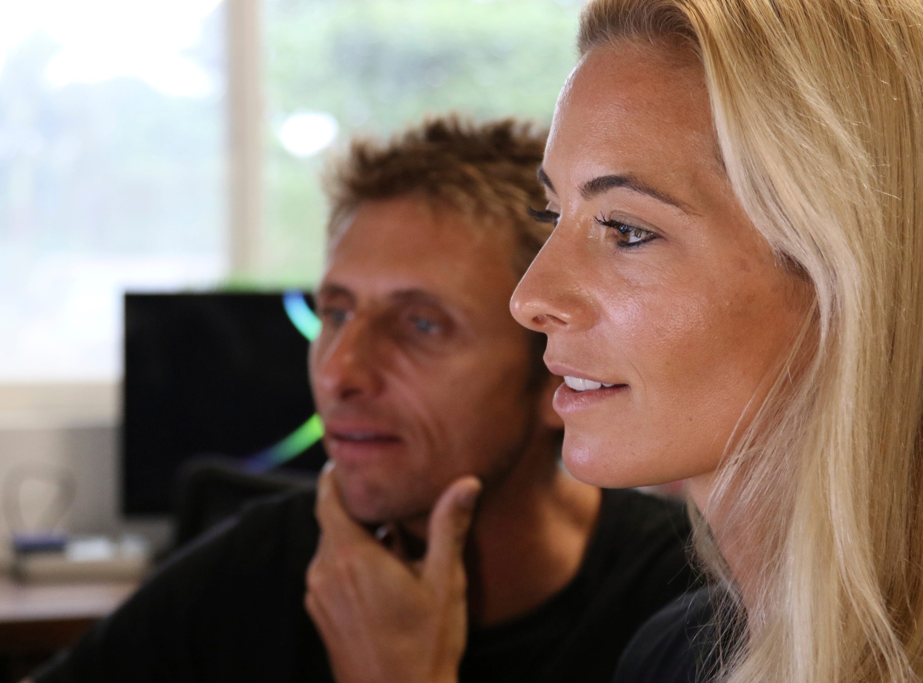 Juan Oliphant, left, and Ocean Ramsey, co-founders of One Ocean Diving and Research, look at footage their encounter with a great white shark, Thursday, Jan. 17, 2019 in Haleiwa, Hawaii.  The two shark researchers who came face-to-face with what could be one of the largest great whites ever recorded, are using their encounter as an opportunity push for legislation that would protect sharks in Hawaii.   (AP Photo/Caleb Jones)