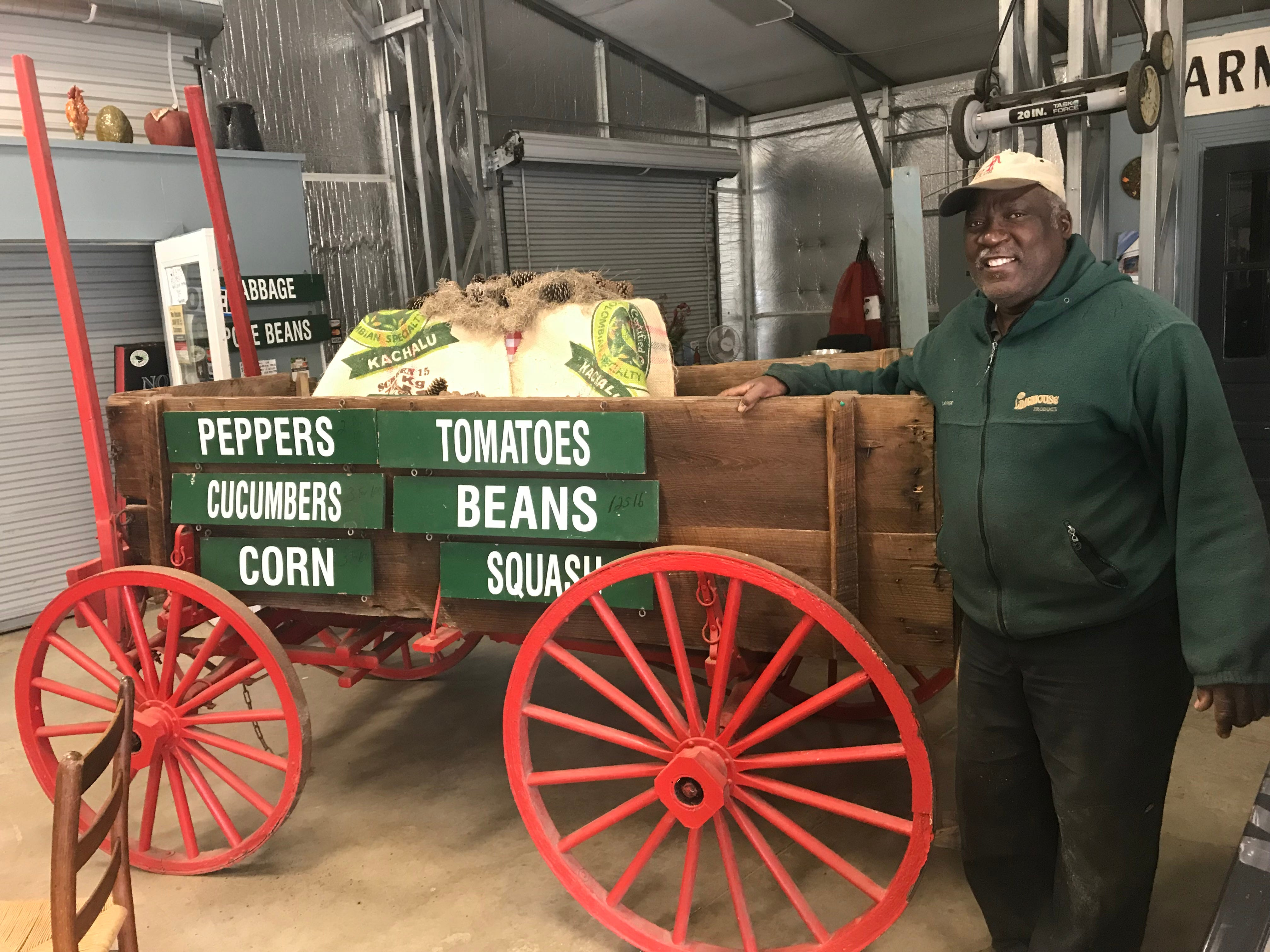 Joseph Fields stands inside his family farm's market next to a cart that's been in the family for generations.