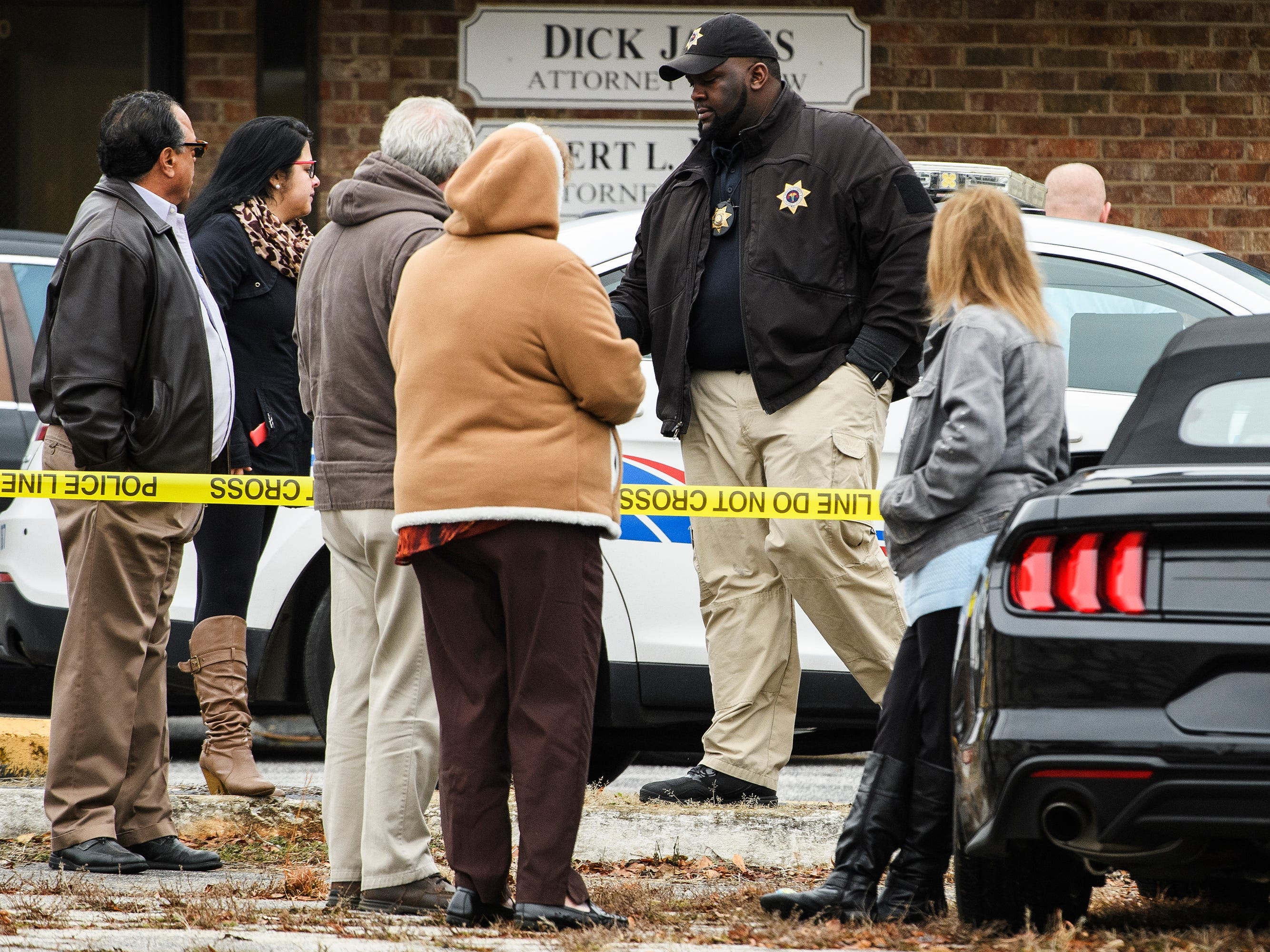 Gary Sessions of the Greenville County Coroner's Office hands out to business cards to loved ones of a man whose death Sessions was investigating on Monday, Jan. 14, 2019