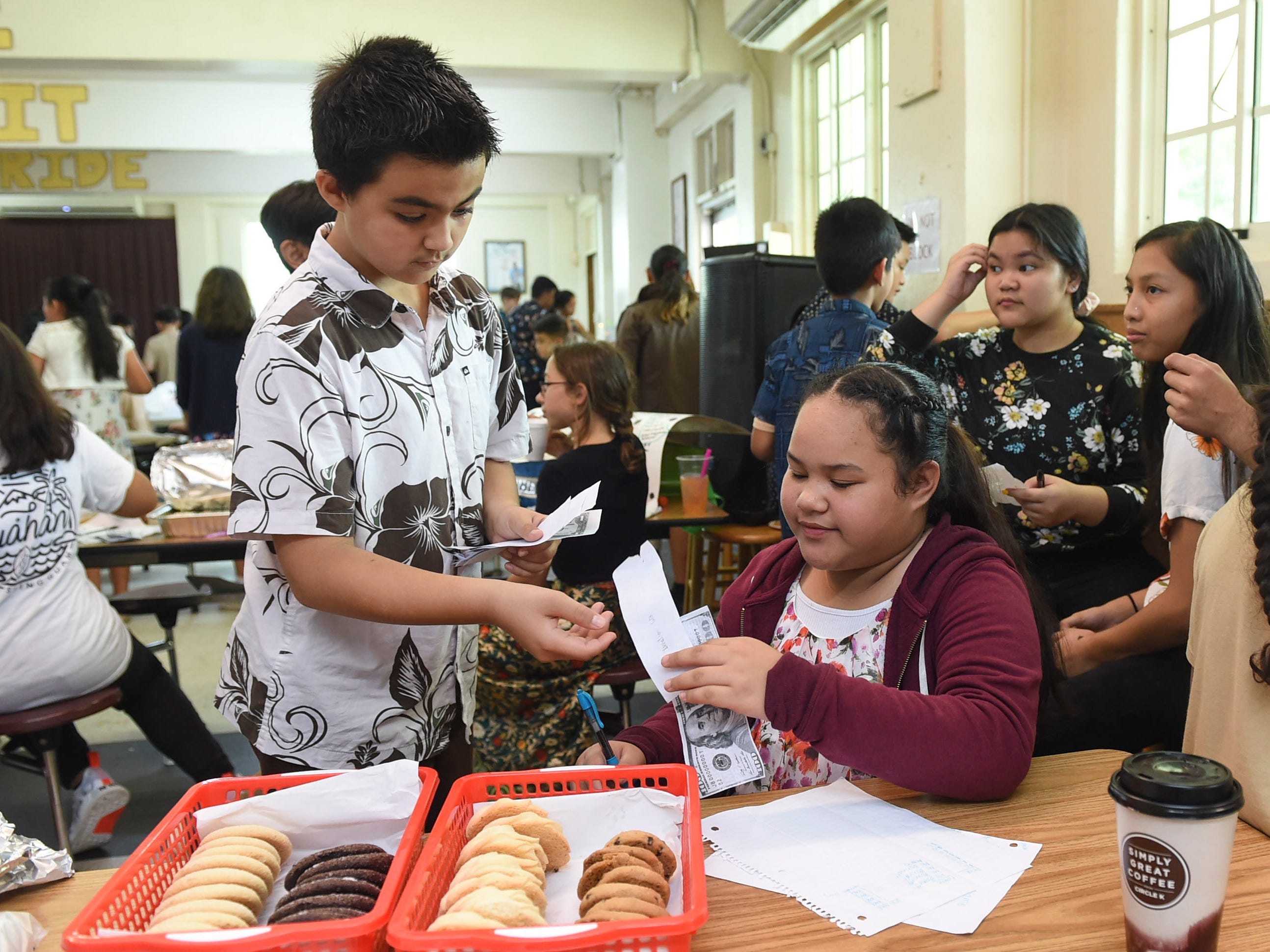 Sixth-grader Alaynan Atalig, 11, collects a payment at her cookie stand during the 5th Annual Ysrael School of Business Retail Bazaar and Entrepreneur Fair at Our Lady of Mount Carmel Catholic School in Agat, Jan. 18, 2019.