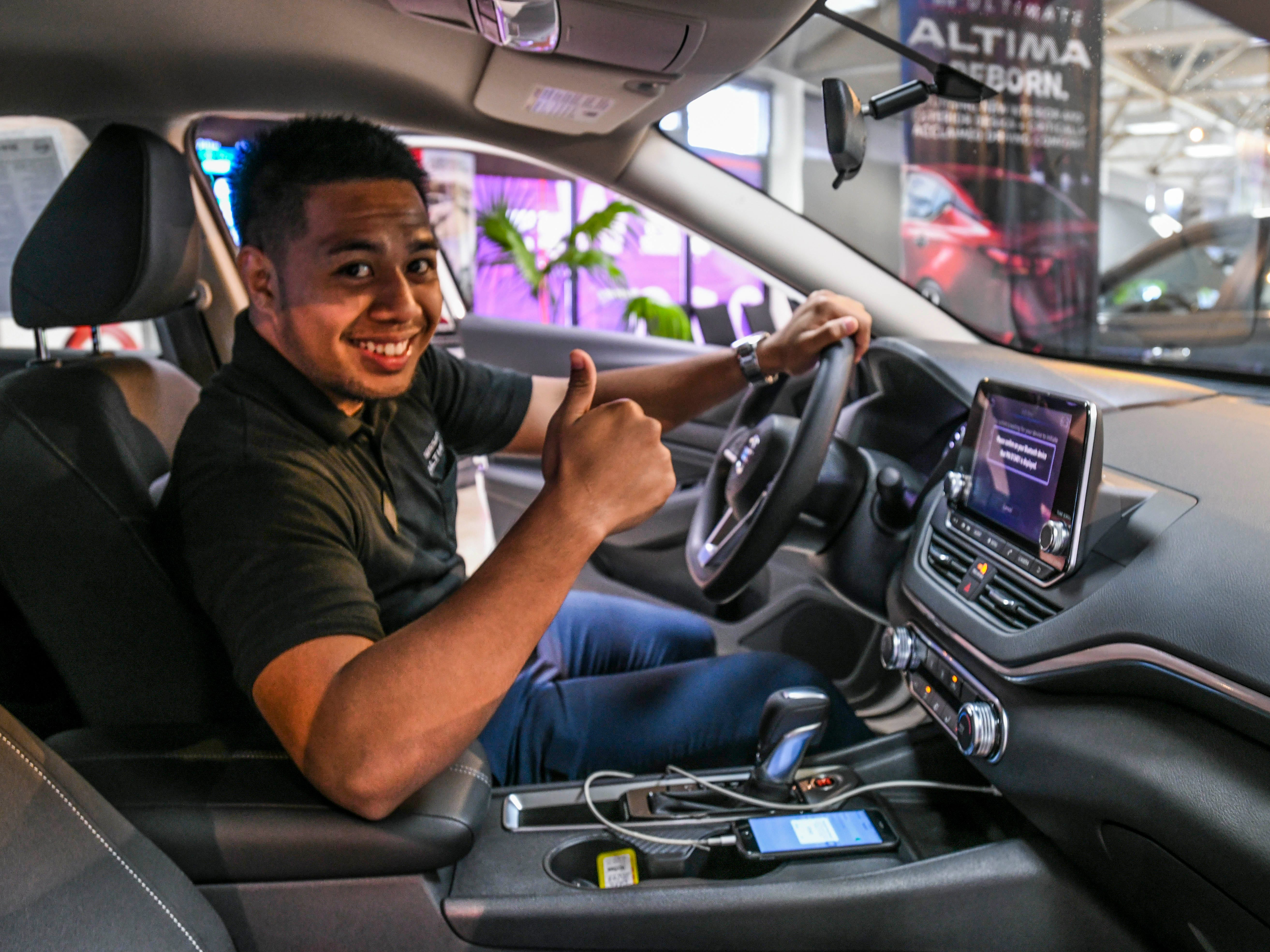 Eddie Wagthuth, a sales consultant at Nissan Guam, gives his approval for the Apple CarPlay feature that could be found in the redesigned 2019 Nissan Altima while at the dealership's showroom in upper Tumon on Friday, Jan. 18, 2019. The connectivity option allows a user to transfer the operations for the applications on their mobile iOS phone to the vehicle's seven-inch Advanced Drive Assist Display, Wagthuth said.