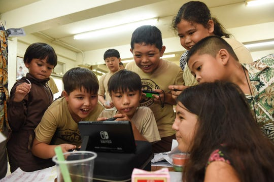 Elementary schoolers gather around Cyril's Smash/Kart game stand during the 5th Annual Ysrael School of Business Retail Bazaar and Entrepreneur Fair at Our Lady of Mount Carmel Catholic School in Agat, Jan. 18, 2019.