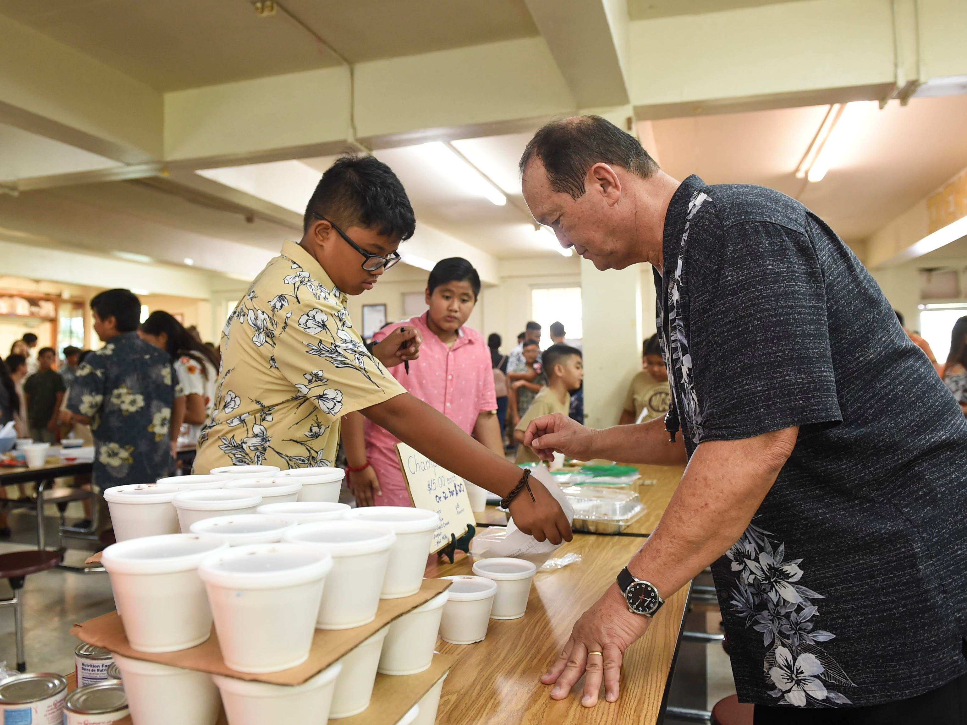 Raenier Perez, 12, makes a champorado sale to Principal Bill Sarmiento during the 5th Annual Ysrael School of Business Retail Bazaar and Entrepreneur Fair at Our Lady of Mount Carmel Catholic School in Agat, Jan. 18, 2019.