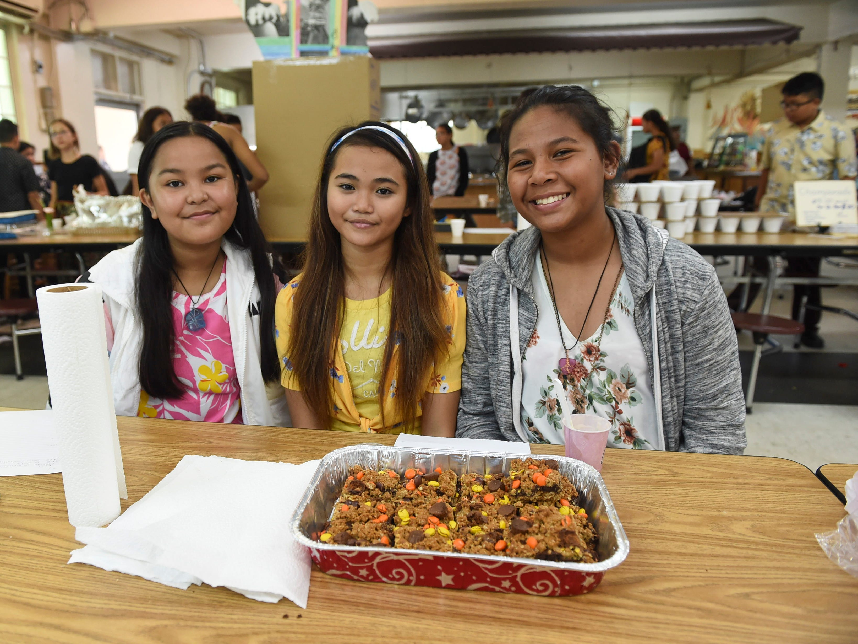 Seventh-grade students Malia Luty, 12, left, Hollie Mutzner, 12, center, and Veronique Pong, 12, during the 5th Annual Ysrael School of Business Retail Bazaar and Entrepreneur Fair at Our Lady of Mount Carmel Catholic School in Agat, Jan. 18, 2019.