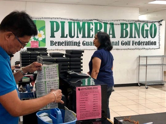 An employee prepares for the start of Bingo games at Plumeria Bingo in Tamuning on Friday.