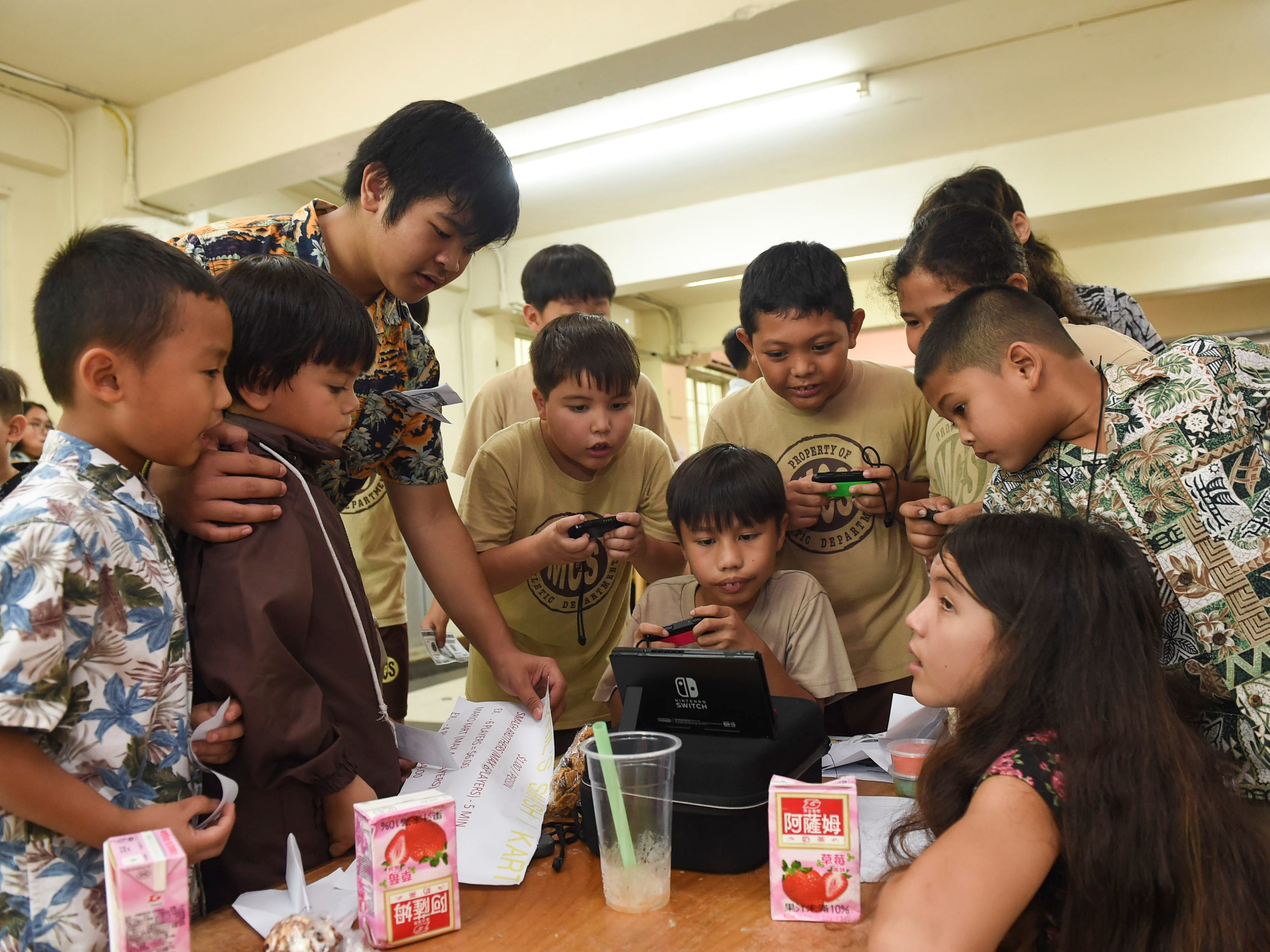 Elementary schoolers gather to play a Nintendo Switch game at 8th-grader Cyril Gustilo's, top left, game stand during the 5th Annual Ysrael School of Business Retail Bazaar and Entrepreneur Fair at Our Lady of Mount Carmel Catholic School in Agat, Jan. 18, 2019.
