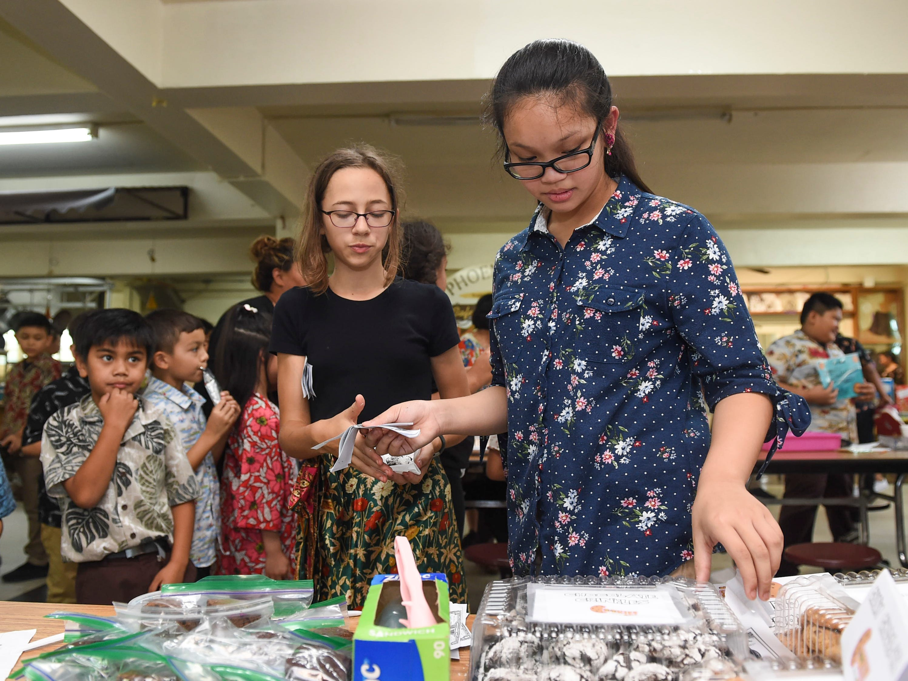 Chloe Vidallon, 11, right, makes a chocolate crinkle cookie sale to Zoe Ozerek, 12, during the 5th Annual Ysrael School of Business Retail Bazaar and Entrepreneur Fair at Our Lady of Mount Carmel Catholic School in Agat, Jan. 18, 2019.