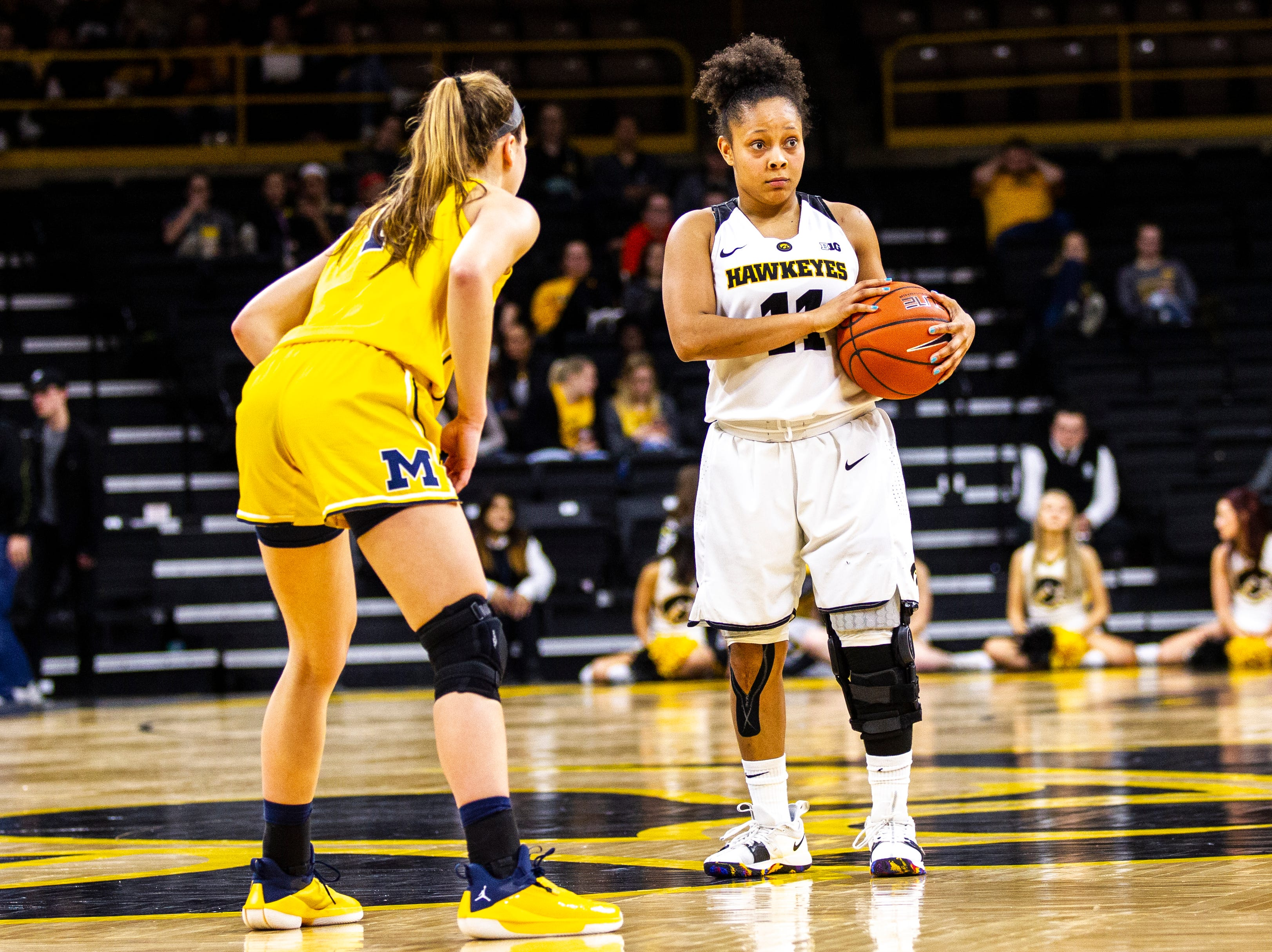 Iowa guard Tania Davis (11) looks to the bench while holding the ball during a NCAA Big Ten Conference women's basketball game on Thursday, Jan. 17, 2019, at Carver-Hawkeye Arena in Iowa City, Iowa.