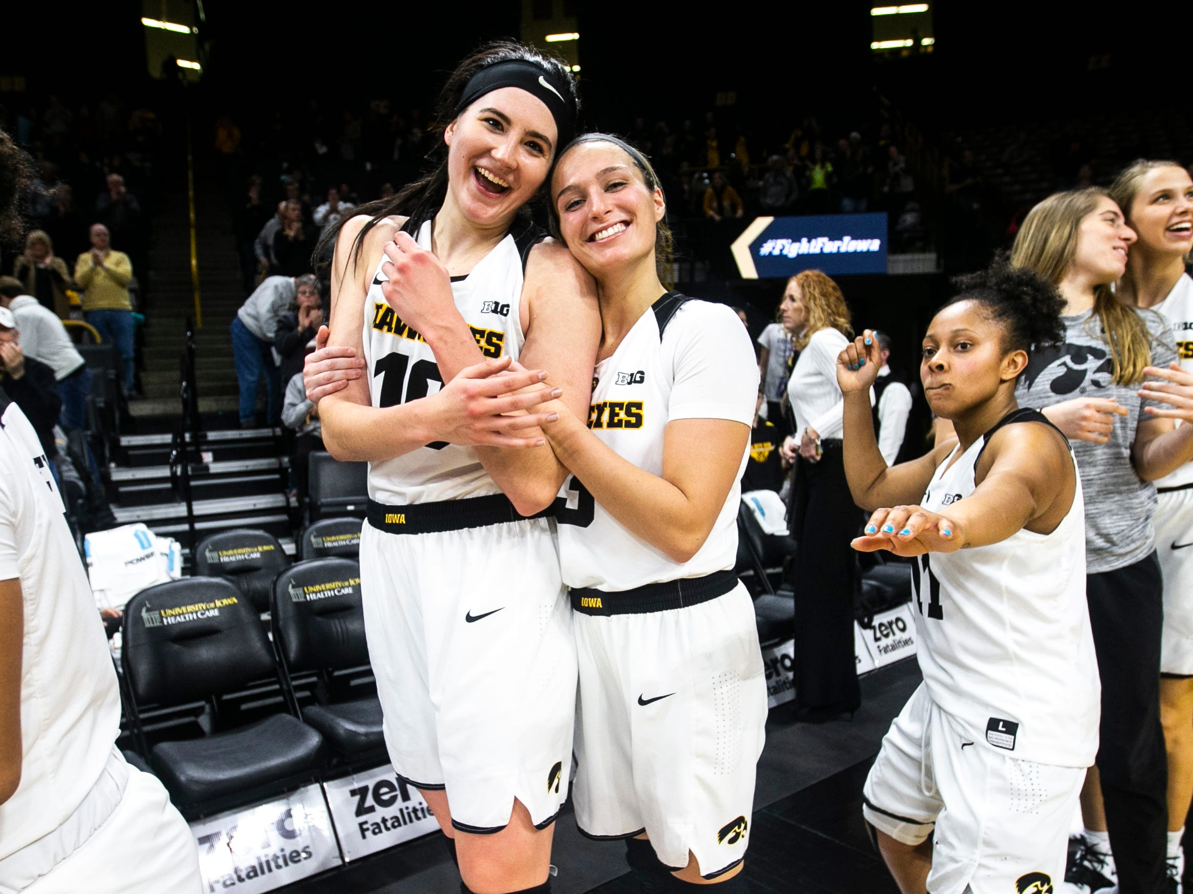 Iowa's Megan Gustafson (10) embraces Makenzie Meyer (3) as Tania Davis (right) dances after a NCAA Big Ten Conference women's basketball game on Thursday, Jan. 17, 2019, at Carver-Hawkeye Arena in Iowa City, Iowa. The Hawkeyes defeated the Wolverines, 75-61.