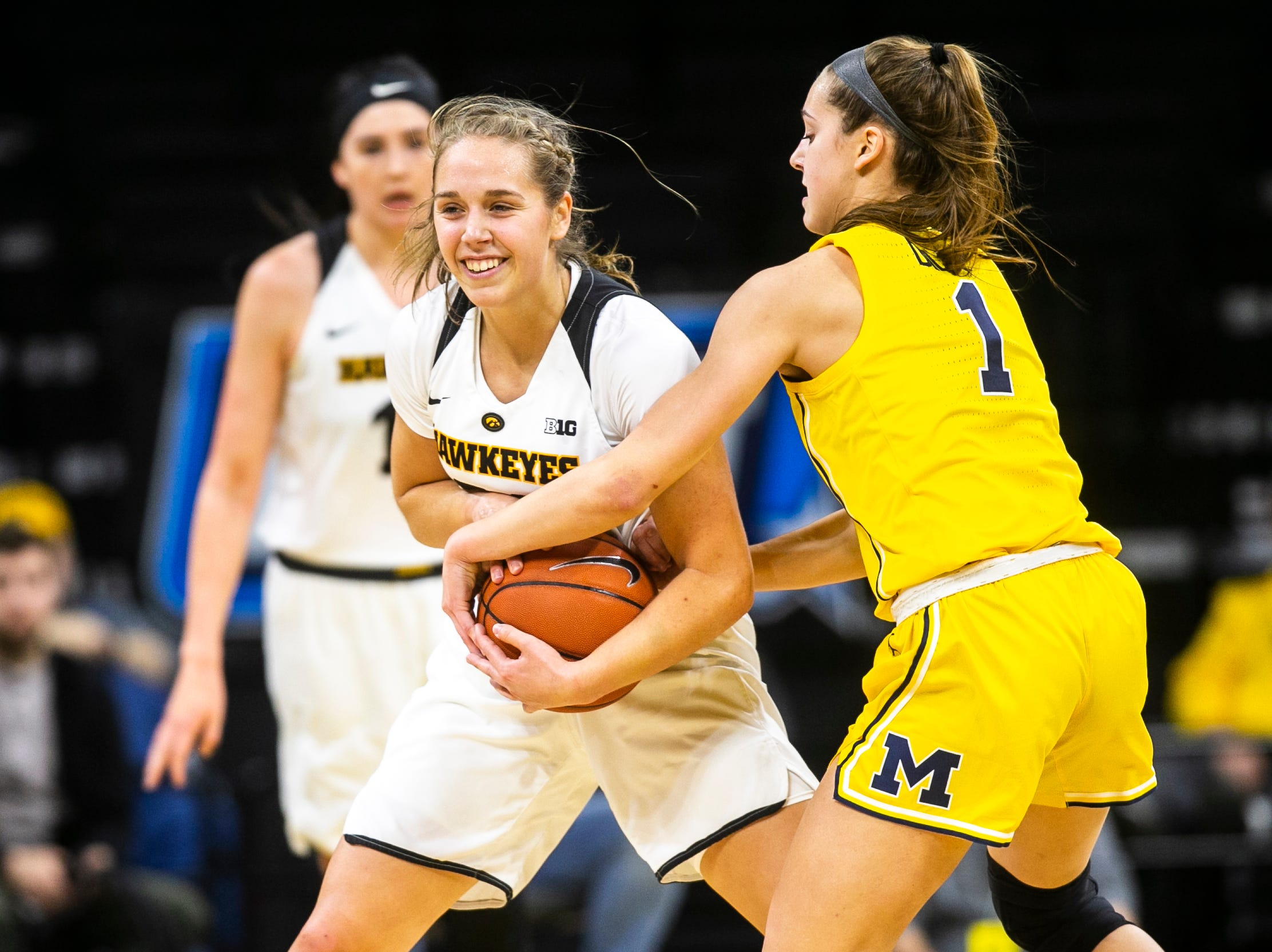 Iowa guard Kathleen Doyle (22) smiles while Michigan guard Amy Dilk (1) reaches in for a jump ball during a NCAA Big Ten Conference women's basketball game on Thursday, Jan. 17, 2019, at Carver-Hawkeye Arena in Iowa City, Iowa.