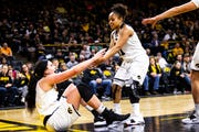 Iowa guard Tania Davis (11) helps up Iowa forward Megan Gustafson (left) during a NCAA Big Ten Conference women's basketball game on Thursday, Jan. 17, 2019, at Carver-Hawkeye Arena in Iowa City, Iowa.