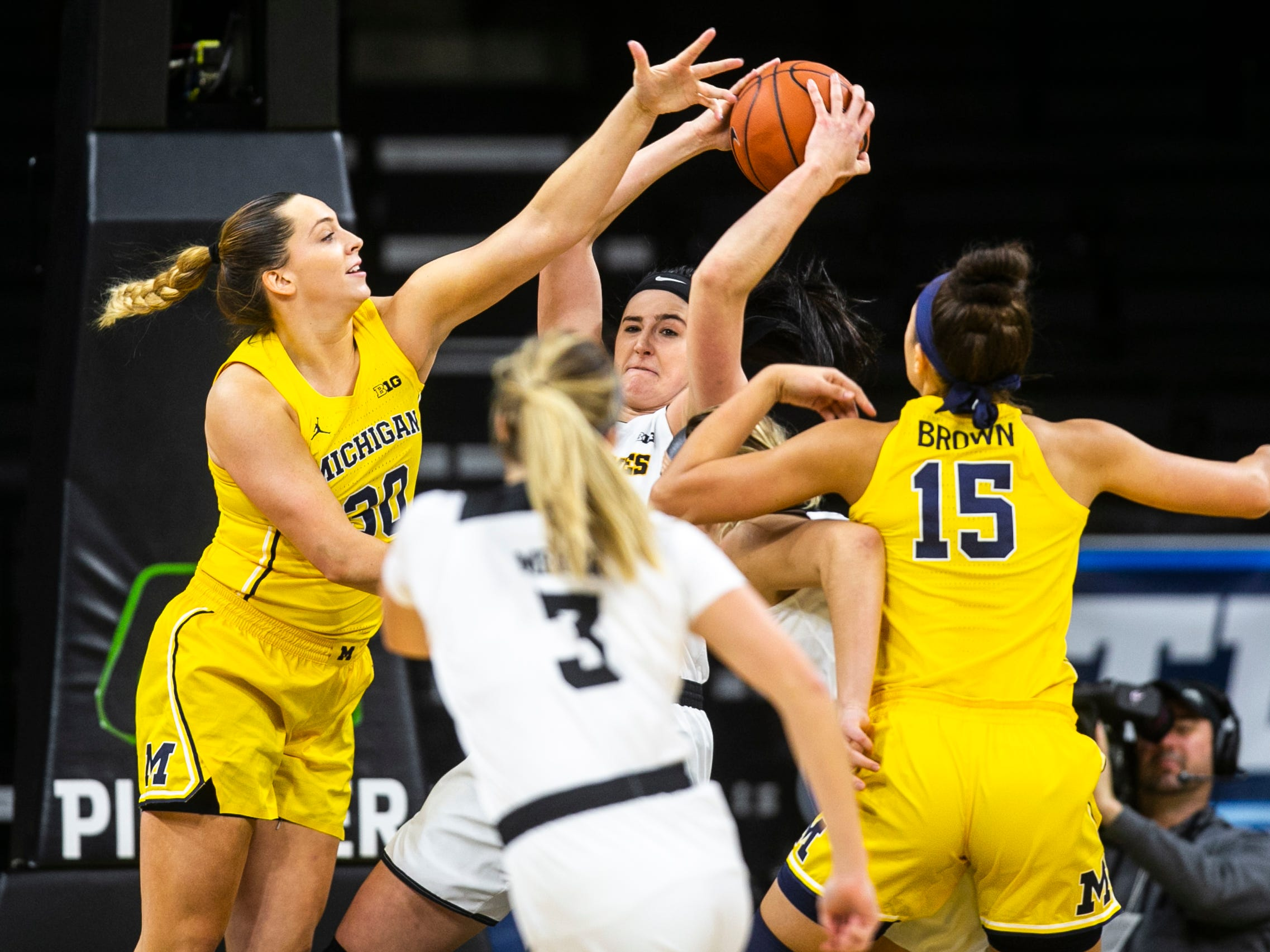 Iowa forward Megan Gustafson (10) pulls down a rebound past Michigan center Hallie Thome (30) and Michigan forward Hailey Brown (15) during a NCAA Big Ten Conference women's basketball game on Thursday, Jan. 17, 2019, at Carver-Hawkeye Arena in Iowa City, Iowa.