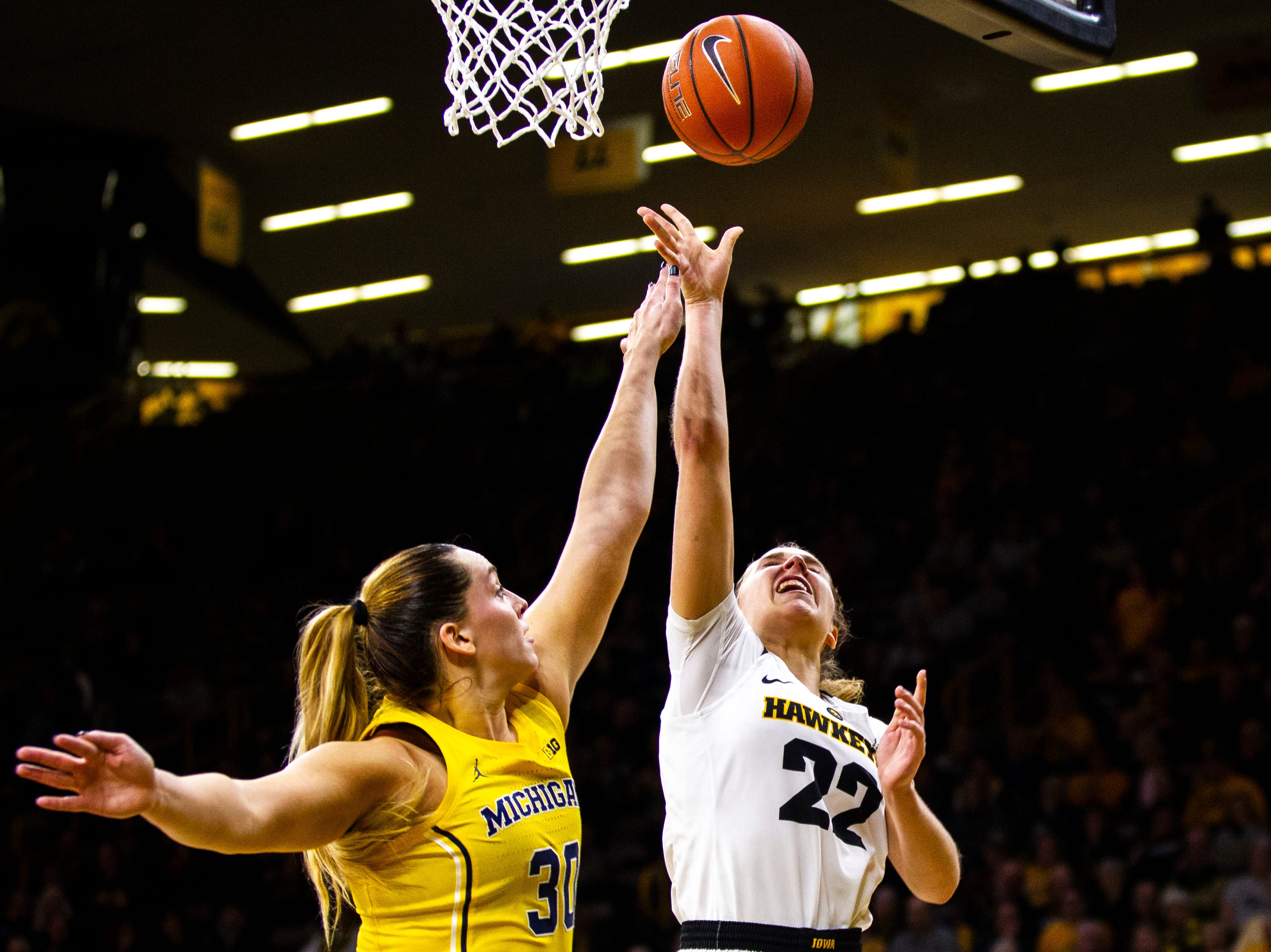 Iowa guard Kathleen Doyle (22) makes a basket past Michigan center Hallie Thome (30) during a NCAA Big Ten Conference women's basketball game on Thursday, Jan. 17, 2019, at Carver-Hawkeye Arena in Iowa City, Iowa.