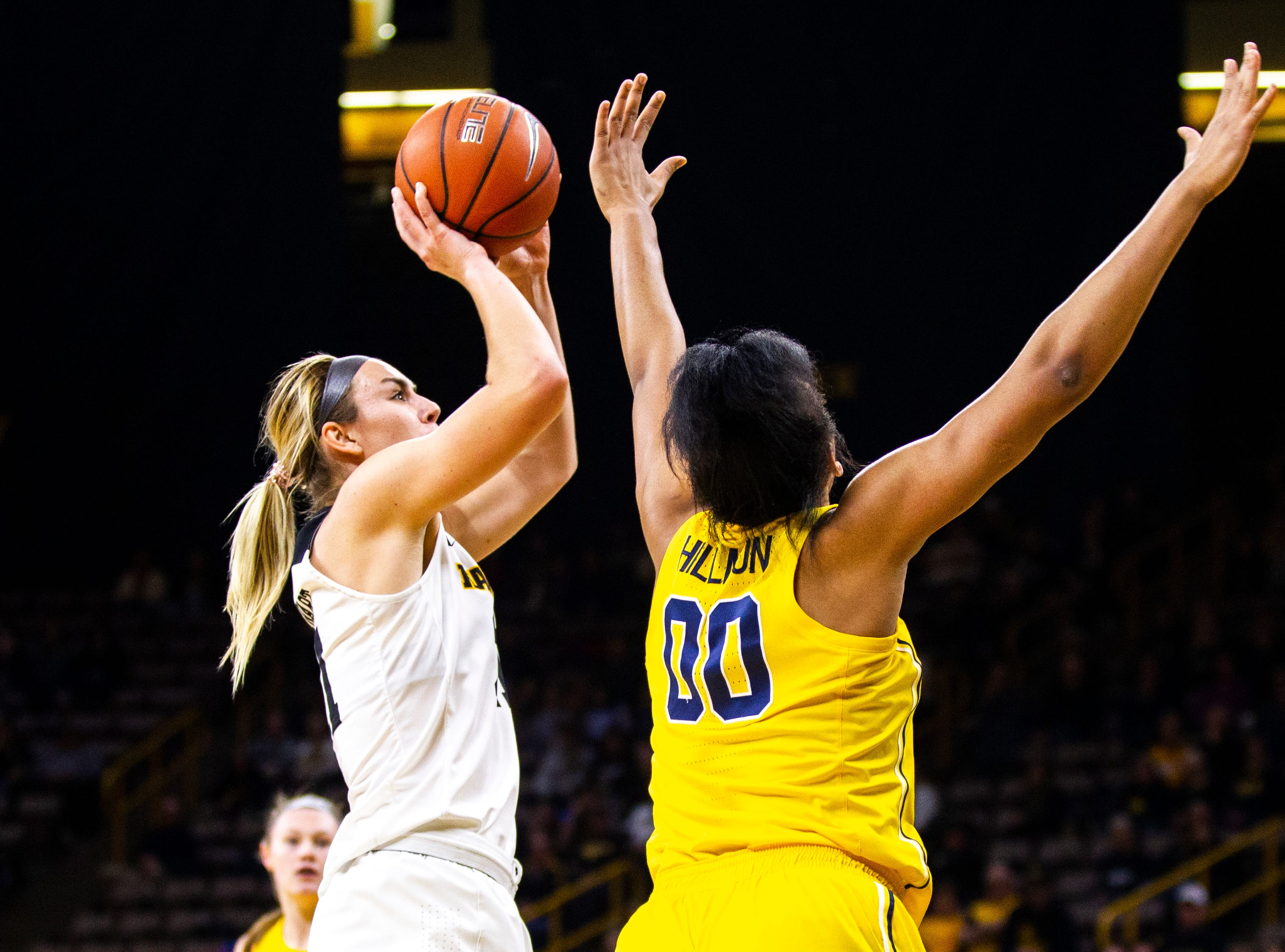 Iowa forward Hannah Stewart (21) attempts a basket while being defended by Michigan forward Naz Hillmon (00) during a NCAA Big Ten Conference women's basketball game on Thursday, Jan. 17, 2019, at Carver-Hawkeye Arena in Iowa City, Iowa.