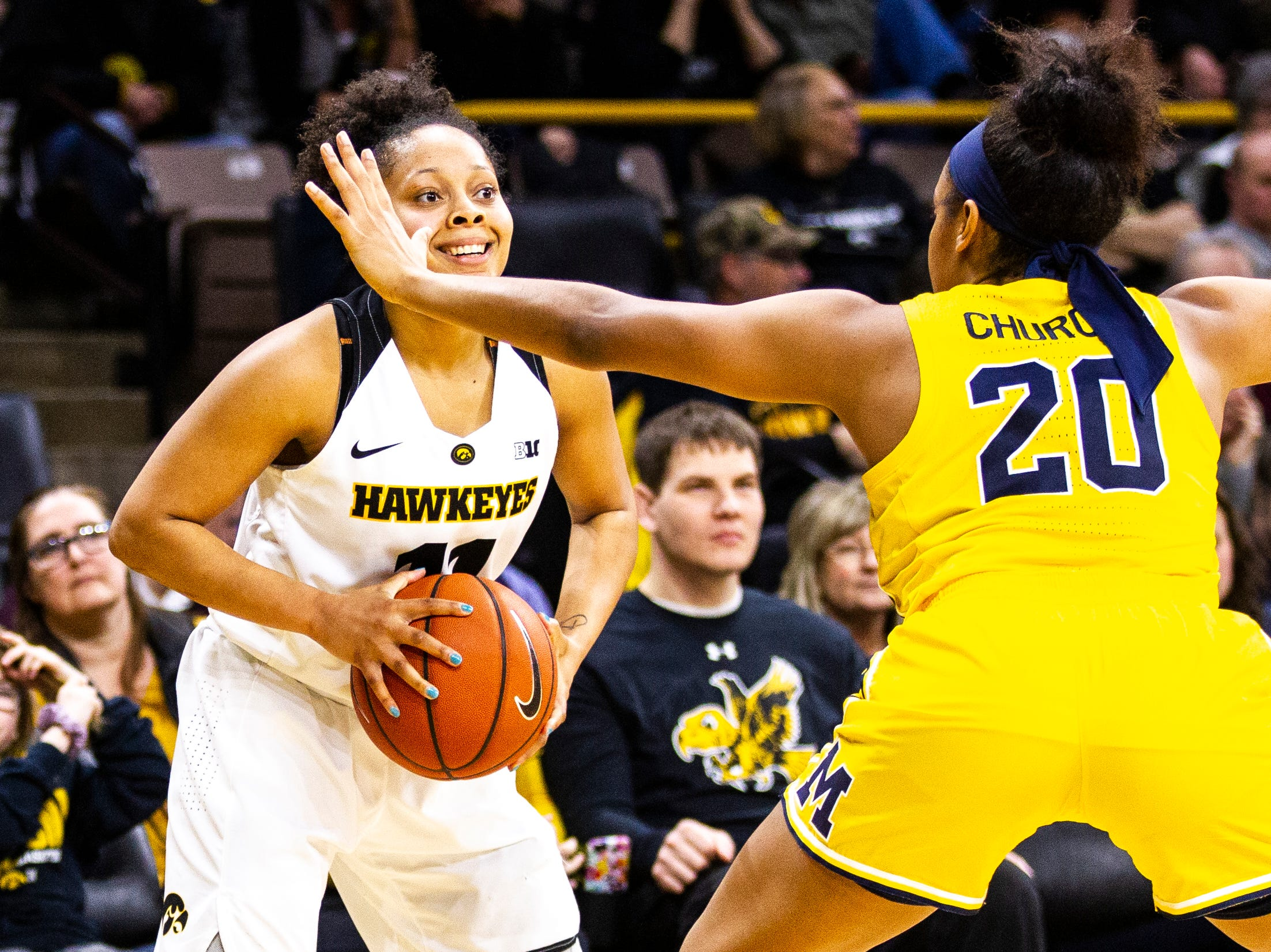 Iowa guard Tania Davis (11) smiles while being defended by Michigan guard Deja Church (20) during a NCAA Big Ten Conference women's basketball game on Thursday, Jan. 17, 2019, at Carver-Hawkeye Arena in Iowa City, Iowa.