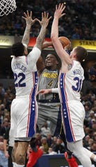 Indiana Pacers guard Victor Oladipo (4) drives on Philadelphia 76ers forward Wilson Chandler (22) and  Mike Muscala (31) in the first half of their game at Bankers Life Fieldhouse on Thursday, Jan. 17, 2019.