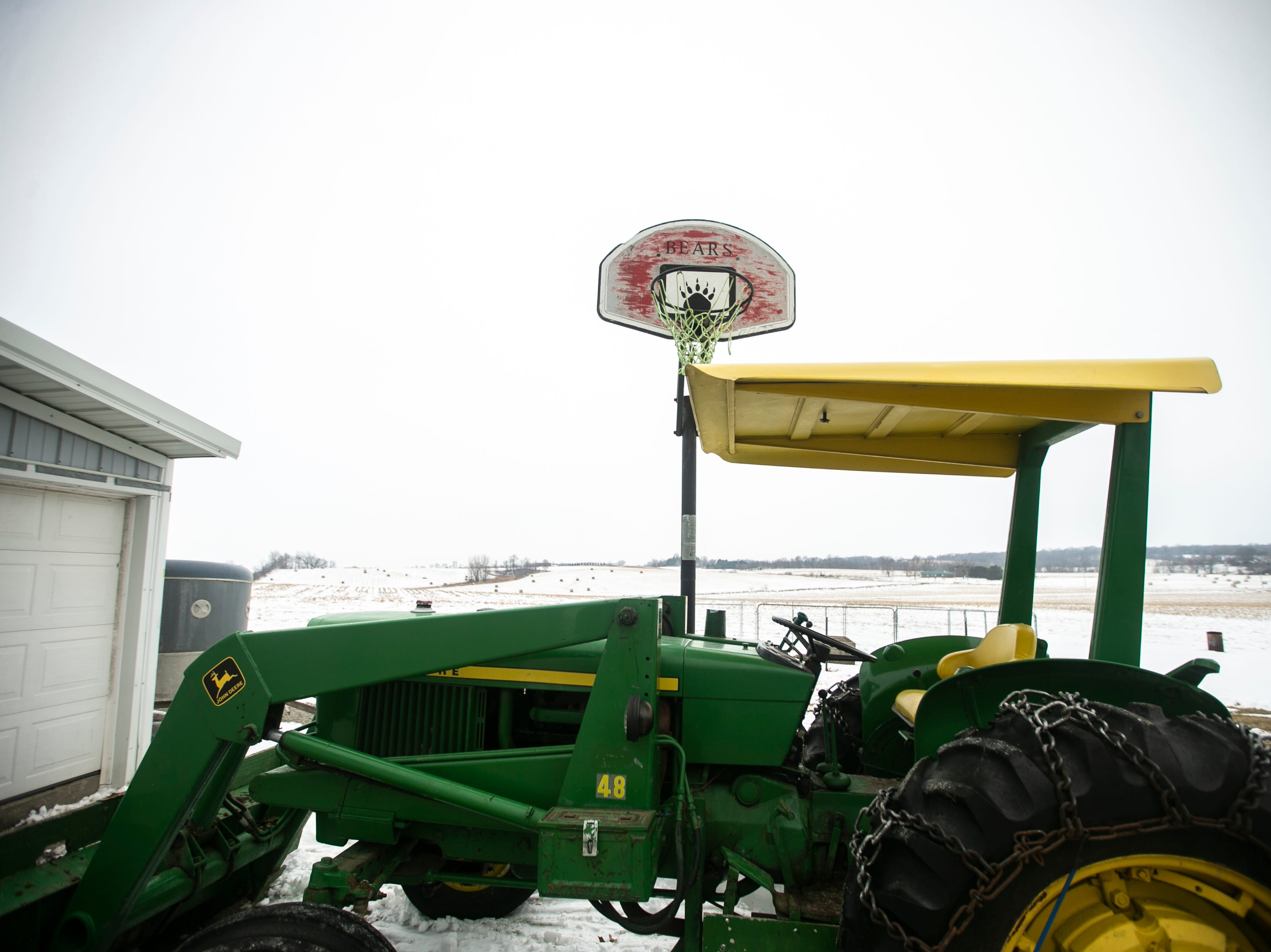 A tractor sits below a West Branch Bears basketball hoop on Thursday, Jan. 17, 2019, at Natural Oak Pork farm in West Branch, Iowa.