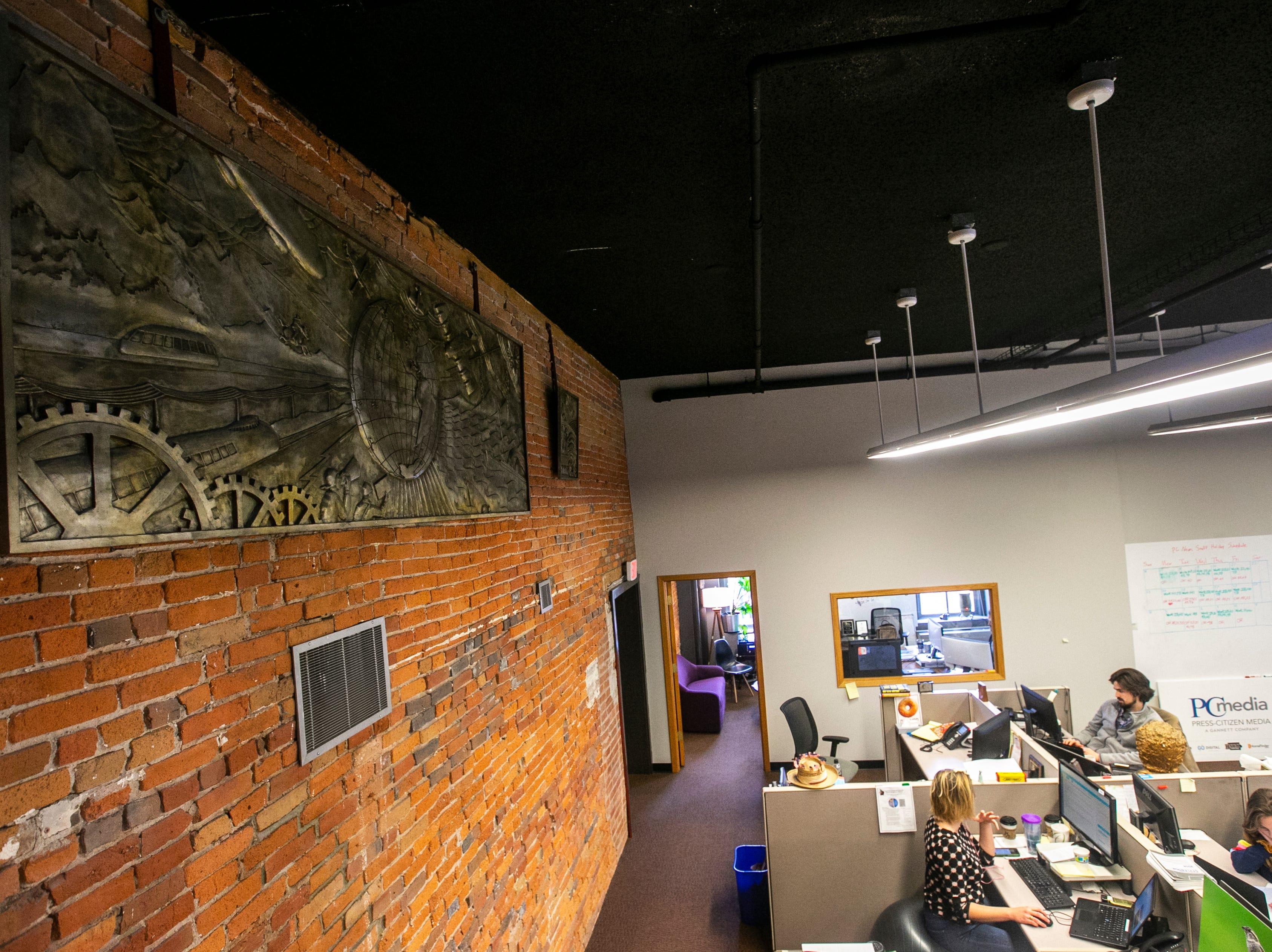 The original bas-relief cement molds from the old Iowa City Press-Citizen building on Washington Street hang in the current newsroom on Friday, Jan. 18, 2019, inside Brewery Square at 123 N. Linn Street in Iowa City, Iowa.