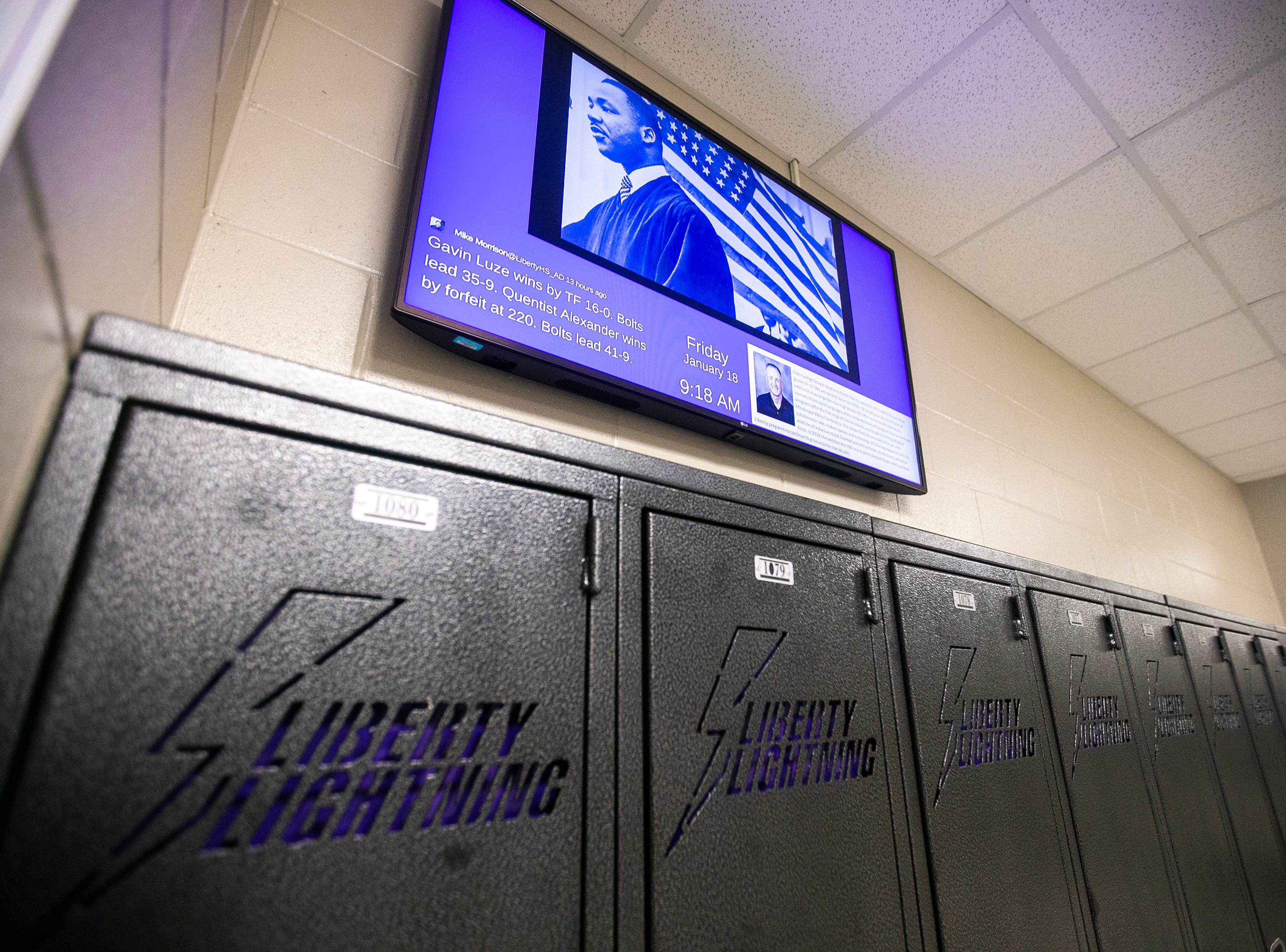 A TV screen hanging above lockers in a hallway displays updates from the school along with a photo of Martin Luther King Jr. during an MLK day event on Friday, Jan. 18, 2019, at Liberty High School in North Liberty, Iowa.