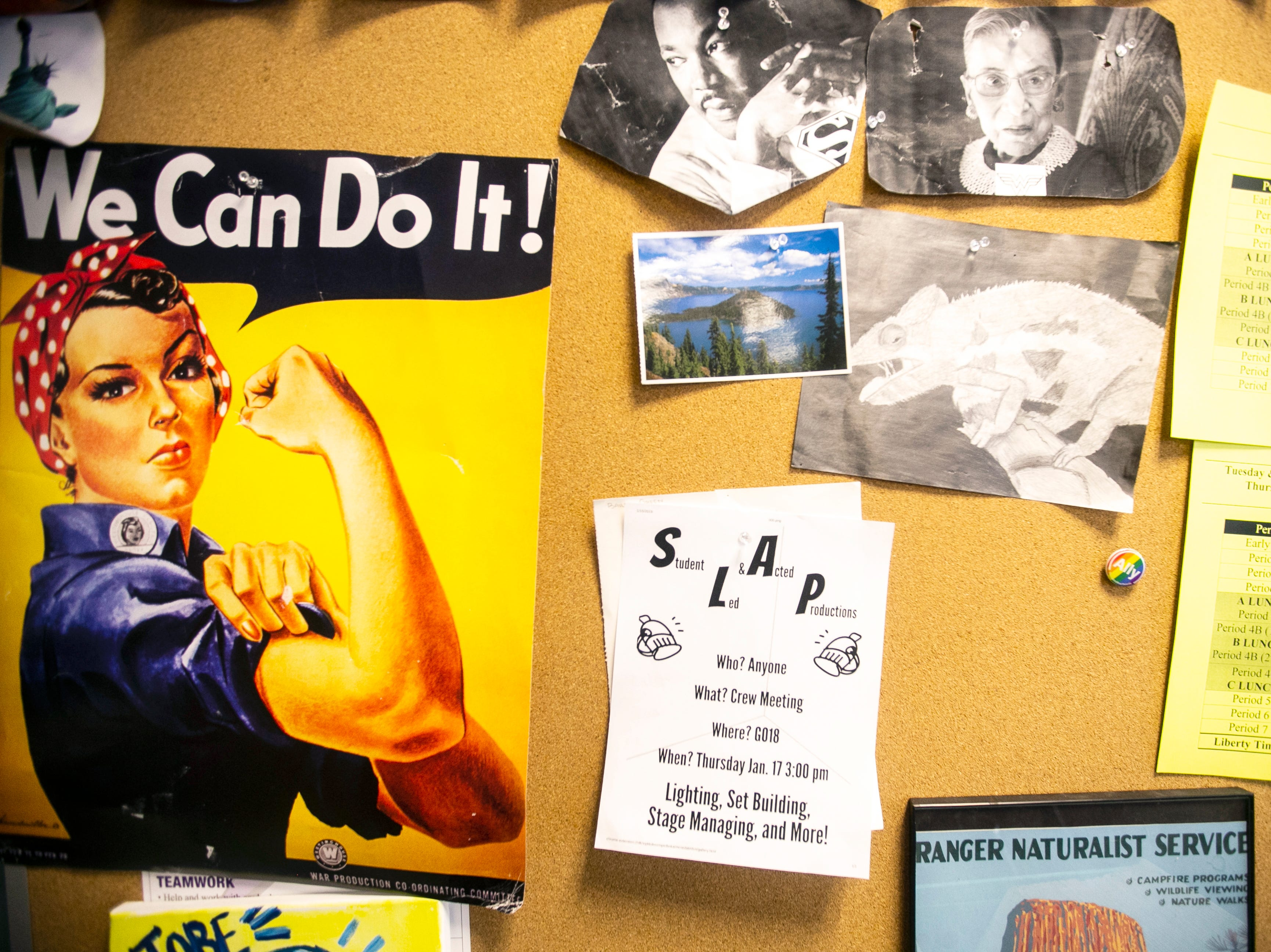 """A bulletin board displays photos of Martin Luther King Jr. and Ruth Bader Ginsburg with superhero logos of Superman and Wonder Woman, respectively, attached to them along with a reproduction poster of Rosie the Riveter with the slogan """"We can do it!"""" are seen during an MLK day event on Friday, Jan. 18, 2019, at Liberty High School in North Liberty, Iowa."""