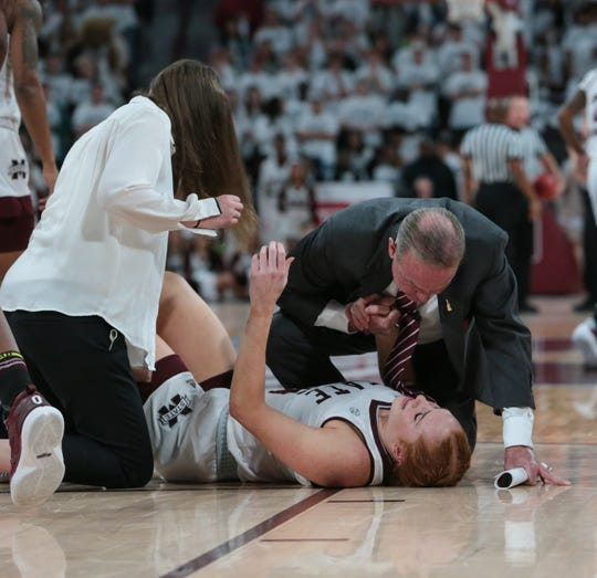 Mississippi State's Vic Schaefer comforts Mississippi State's Chloe Bibby (55) after she suffered an injury early in the game. Mississippi State played South Carolina in a women's SEC basketball game at Humphrey Coliseum on Thursday, January 17, 2019. Photo by Keith Warren