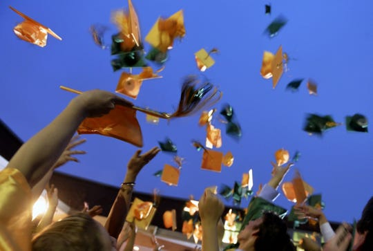 Graduates toss their caps in the air after commencement.