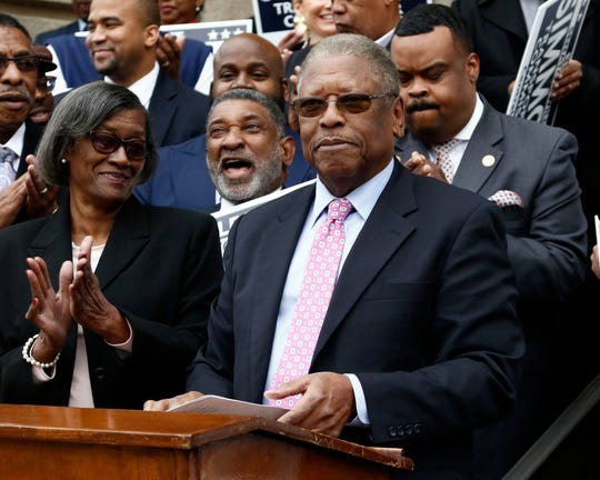 Rep. Oscar Denton, D-Vicksburg, background center, cheers as others applaud after State Sen. Willie Simmons, D-Cleveland, foreground, announces his candidacy for Transportation Commissioner for the Central District, Thursday, Jan. 17, 2019, in Jackson, Miss.