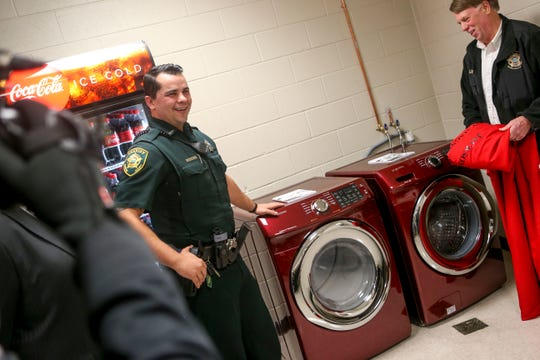 Sheriff's deputy William Haley and Sheriff John Mehr smile after unveiling a new washer and dryer donated to Jackson Careers and Technology Middle School  in Jackson, Tenn., on Friday, Jan. 18, 2019.