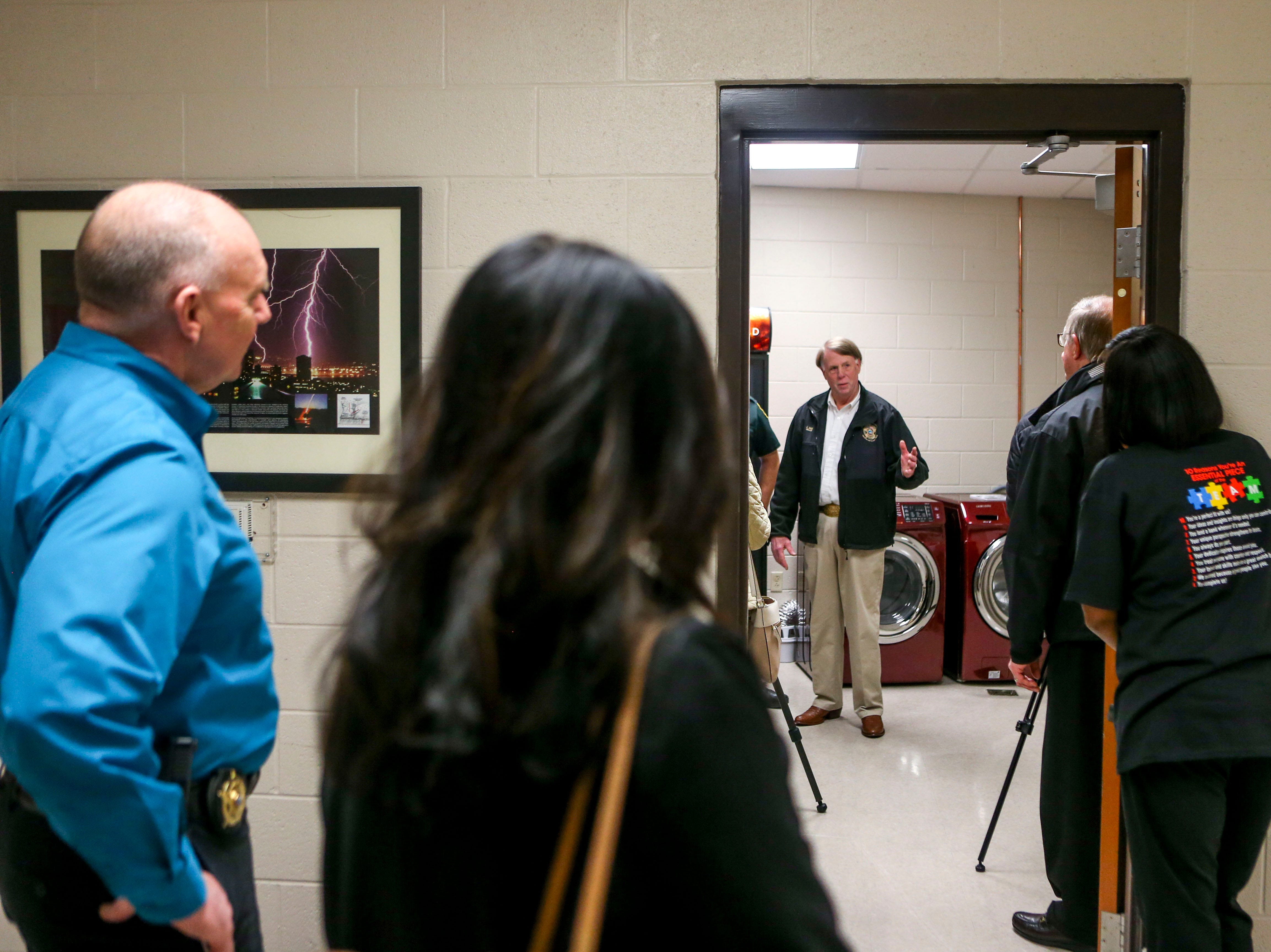 Spectators listen as Sheriff John Mehr speaks in front of a newly donated washer and dryer set with deputy William Haley at Jackson Careers and Technology Middle School  in Jackson, Tenn., on Friday, Jan. 18, 2019.