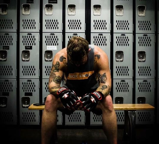 A boxer rests at Title Boxing Club, which offers boxing and kickboxing classes for all skill levels.